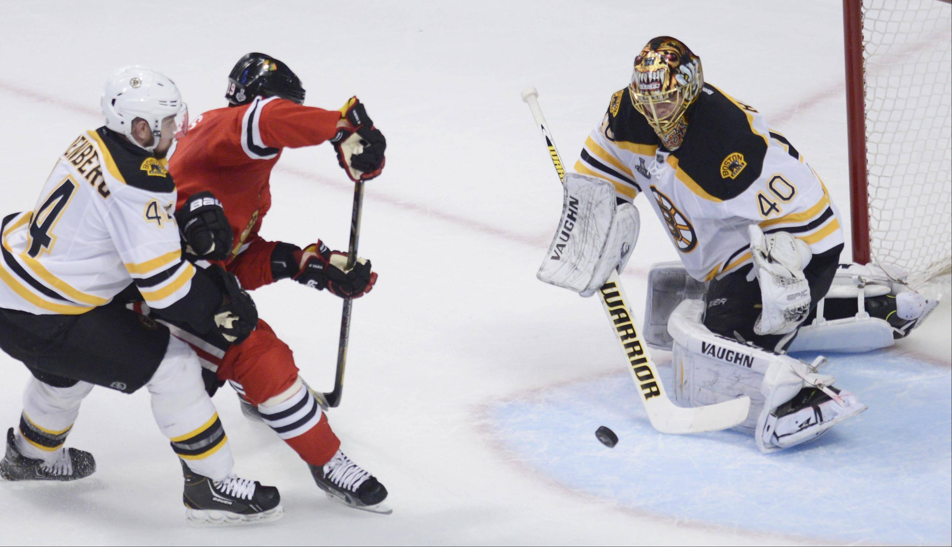 Chicago Blackhawks center Jonathan Toews shoots with Boston Bruins defenseman Dennis Seidenberg on his back.