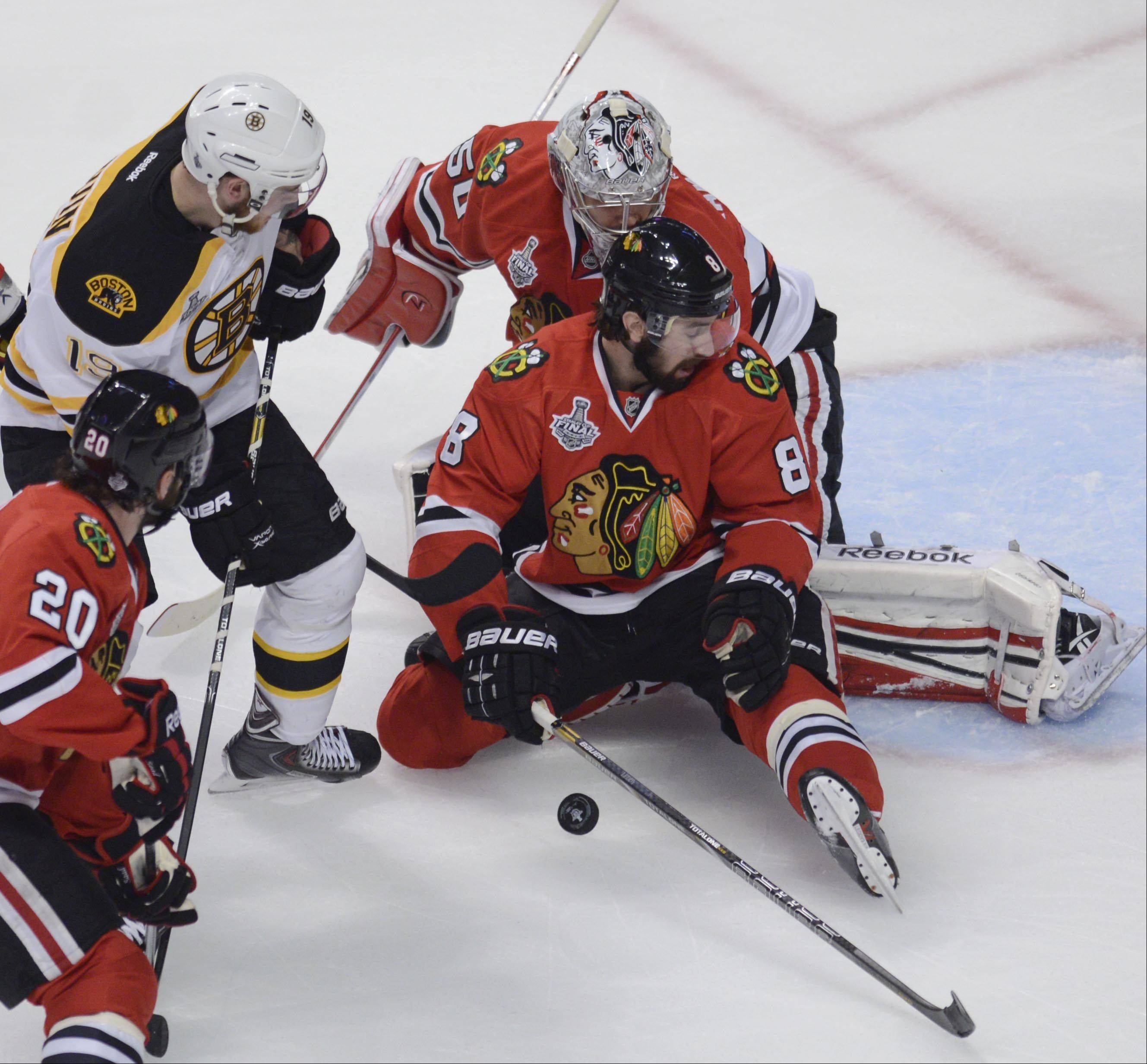 Chicago Blackhawks defenseman Nick Leddy, and goalie Corey Crawford block a shot by Boston Bruins center Tyler Seguin.
