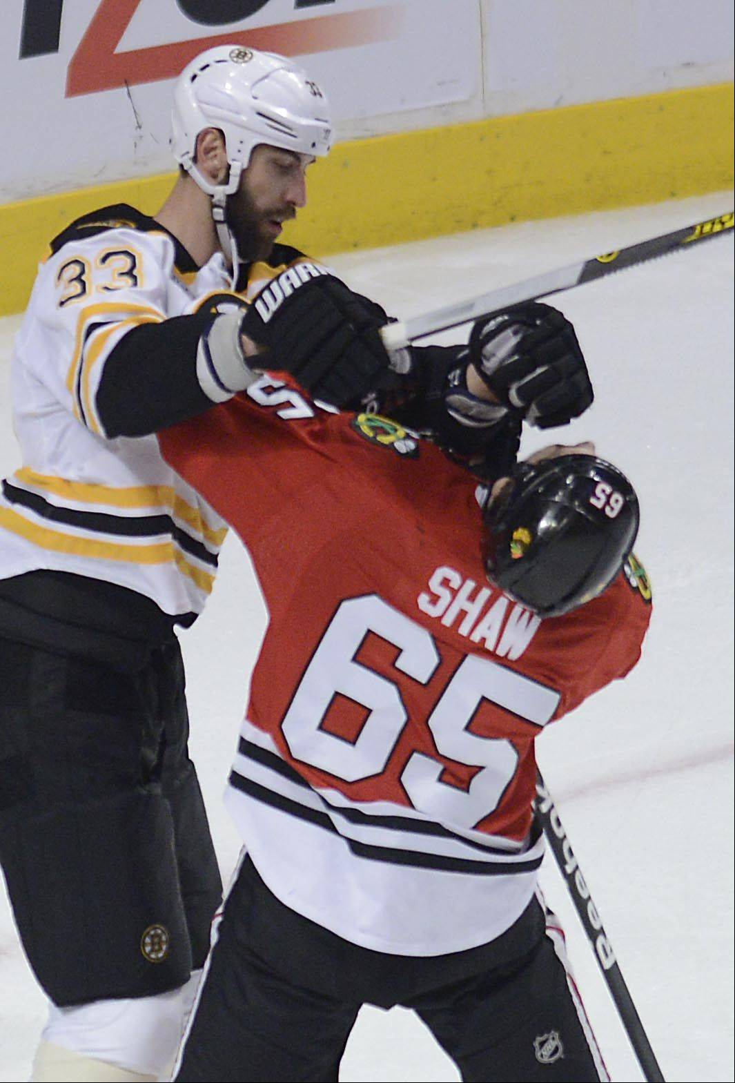 Chicago Blackhawks center Andrew Shaw gets hit in the face by Boston Bruins defenseman Zdeno Chara in the first period.