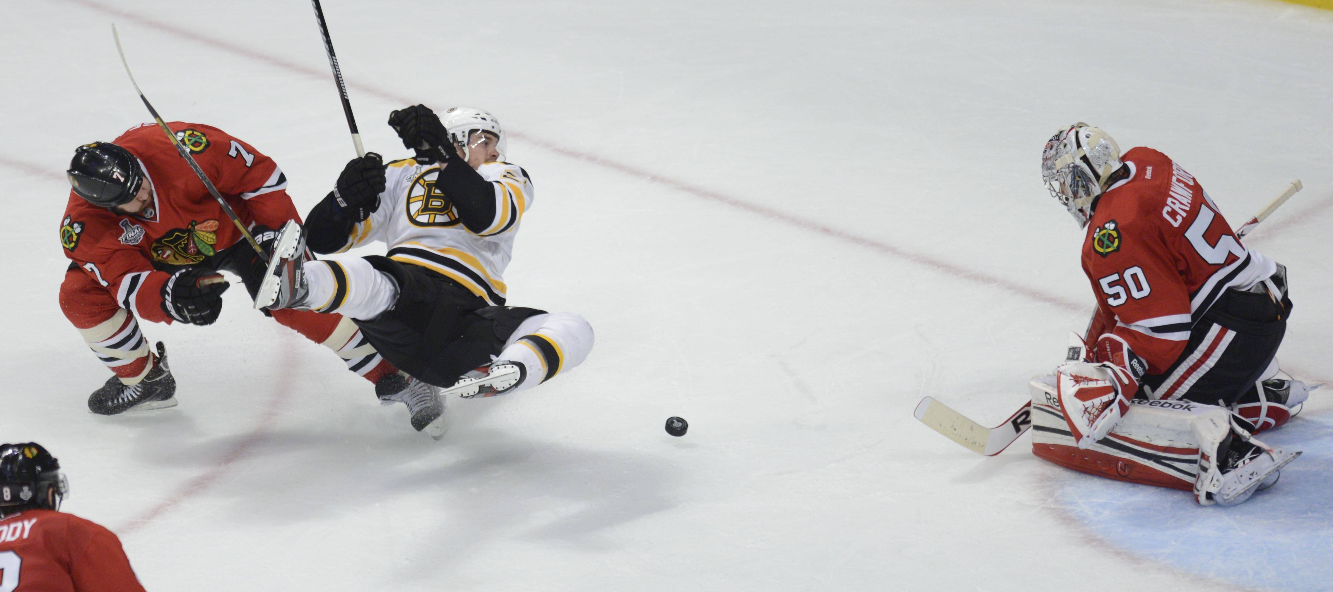 Boston Bruins left wing Daniel Paille flies through the air after colliding with Chicago Blackhawks defenseman Brent Seabrook as he charged the net in the third period during Game 1 of the Stanley Cup Finals Wednesday at the Untied Center in Chicago. He slid into Chicago Blackhawks goalie Corey Crawford but not penalty was called.