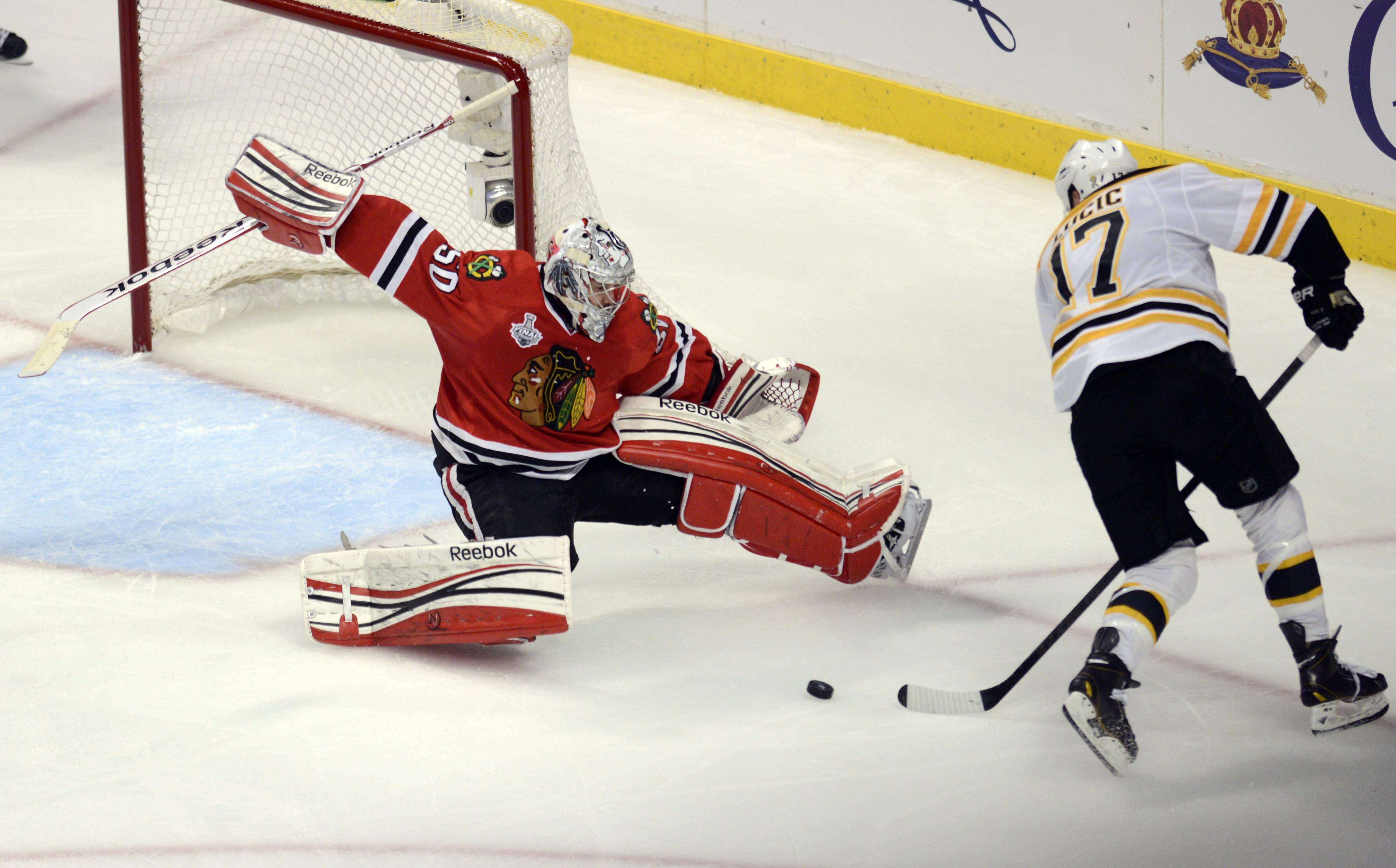Chicago Blackhawks goalie Corey Crawford blocks a shot by Boston Bruins left wing Milan Lucic late in the third period during Game 1 of the Stanley Cup Finals Wednesday at the Untied Center in Chicago.