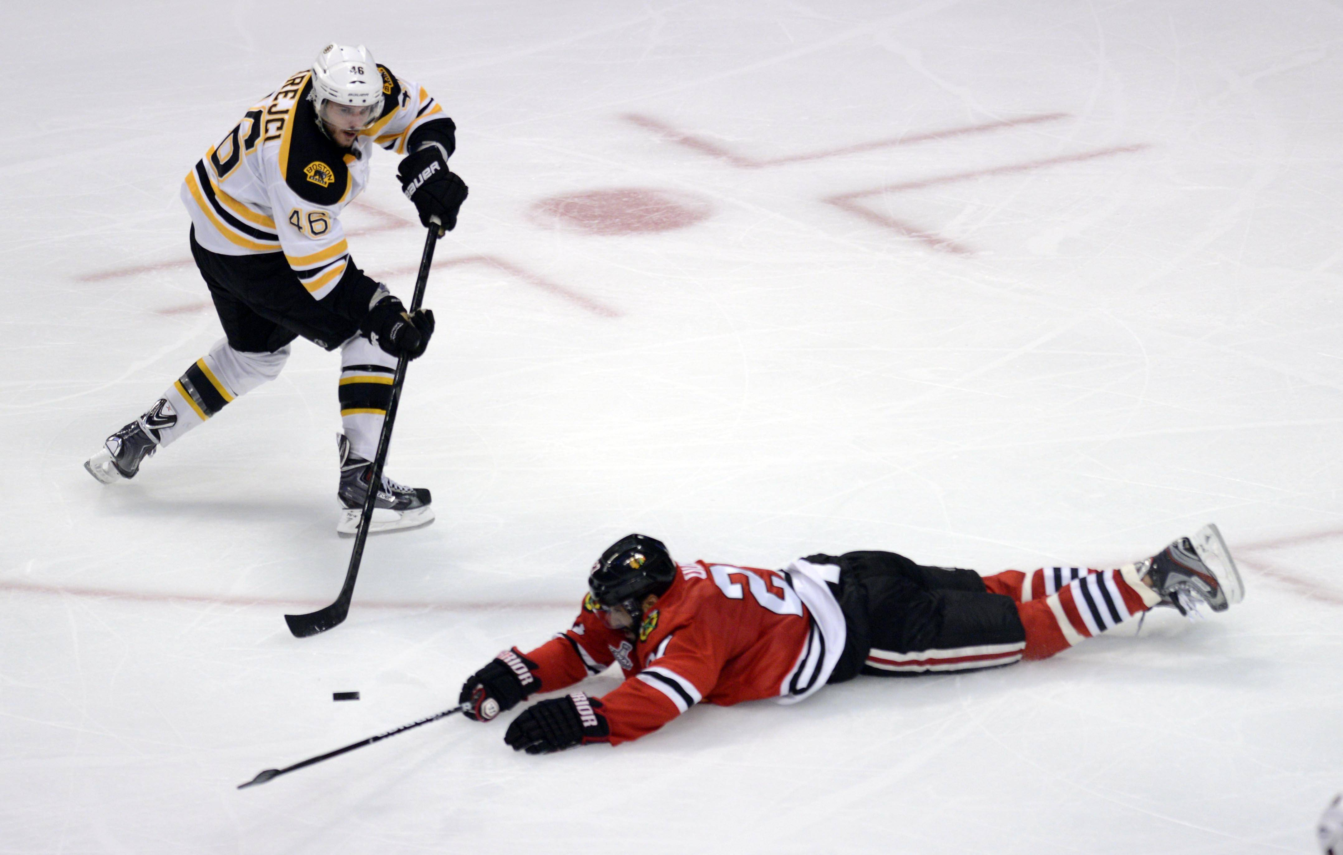 Chicago Blackhawks defenseman Johnny Oduya lays and slides on the ice to block a shot by Boston Bruins center David Krejci in the third period during Game 1 of the Stanley Cup Finals Wednesday at the Untied Center in Chicago.