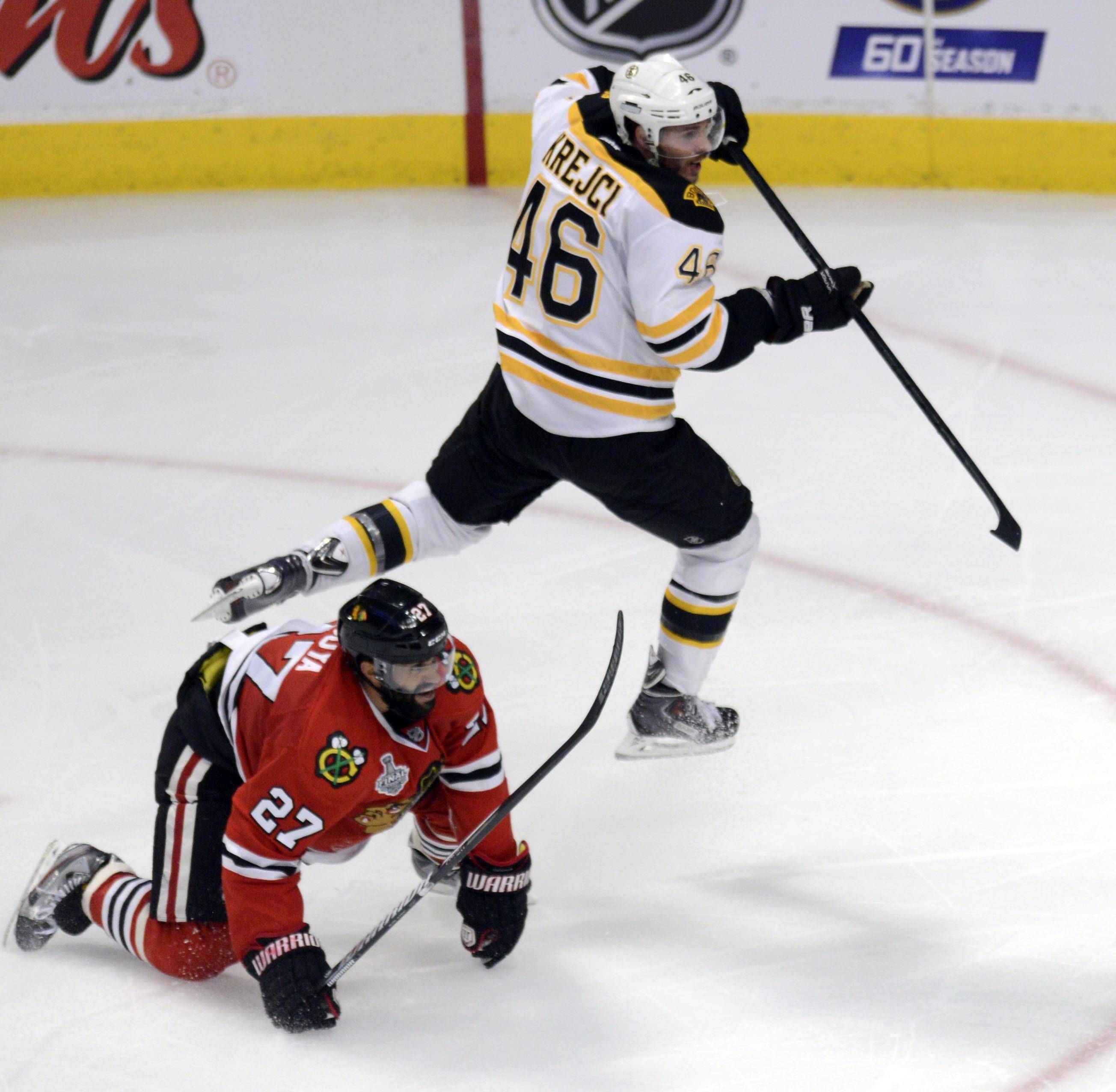 Boston Bruins center David Krejci jumps over Chicago Blackhawks defenseman Johnny Oduya in the third period during Game 1 of the Stanley Cup Finals Wednesday at the Untied Center in Chicago.