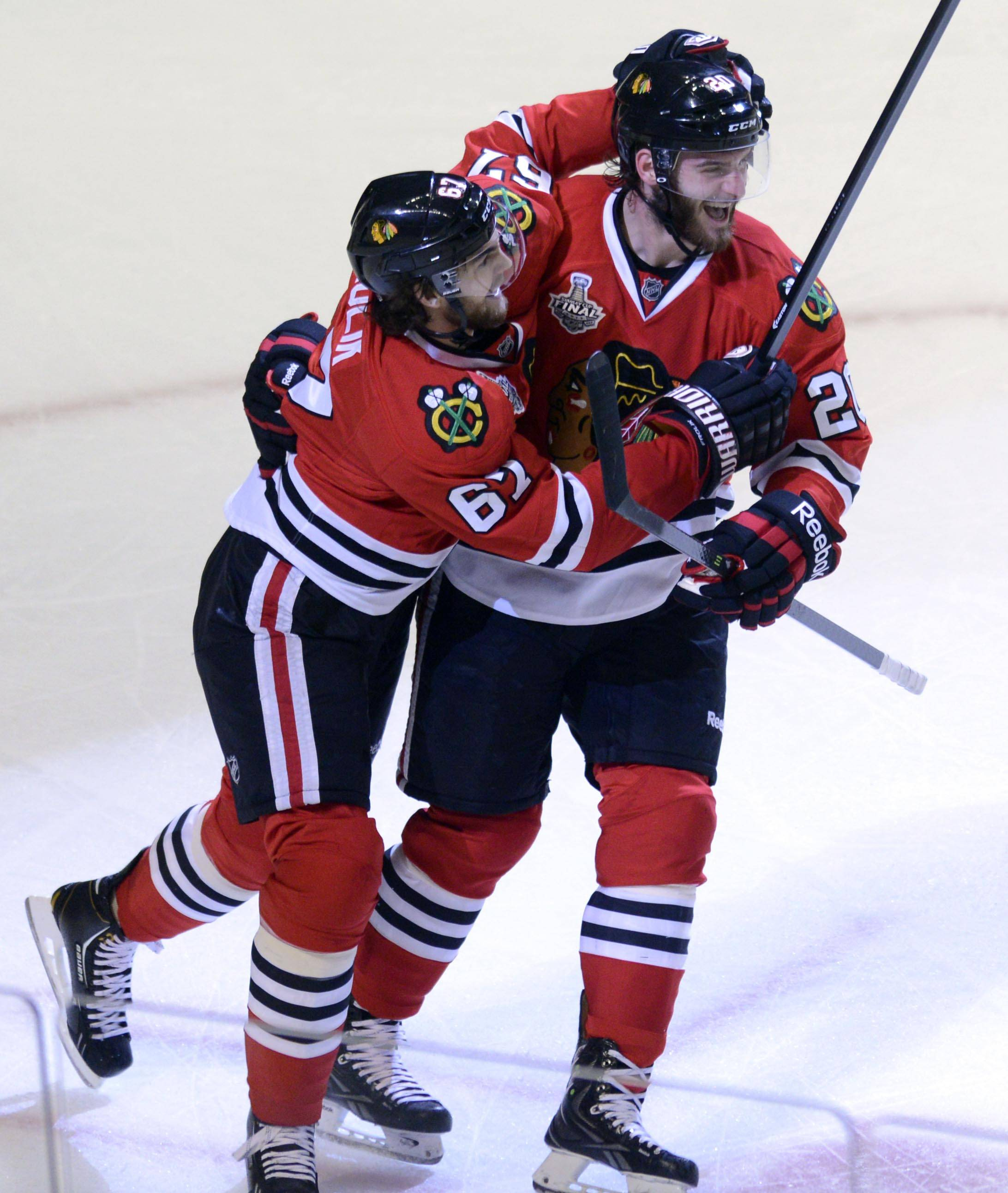 Chicago Blackhawks center Michael Frolik  and left wing Brandon Saad celebrate the tying goal in regulation against the Boston Bruins during Game 1 of the Stanley Cup Finals Wednesday at the Untied Center in Chicago.
