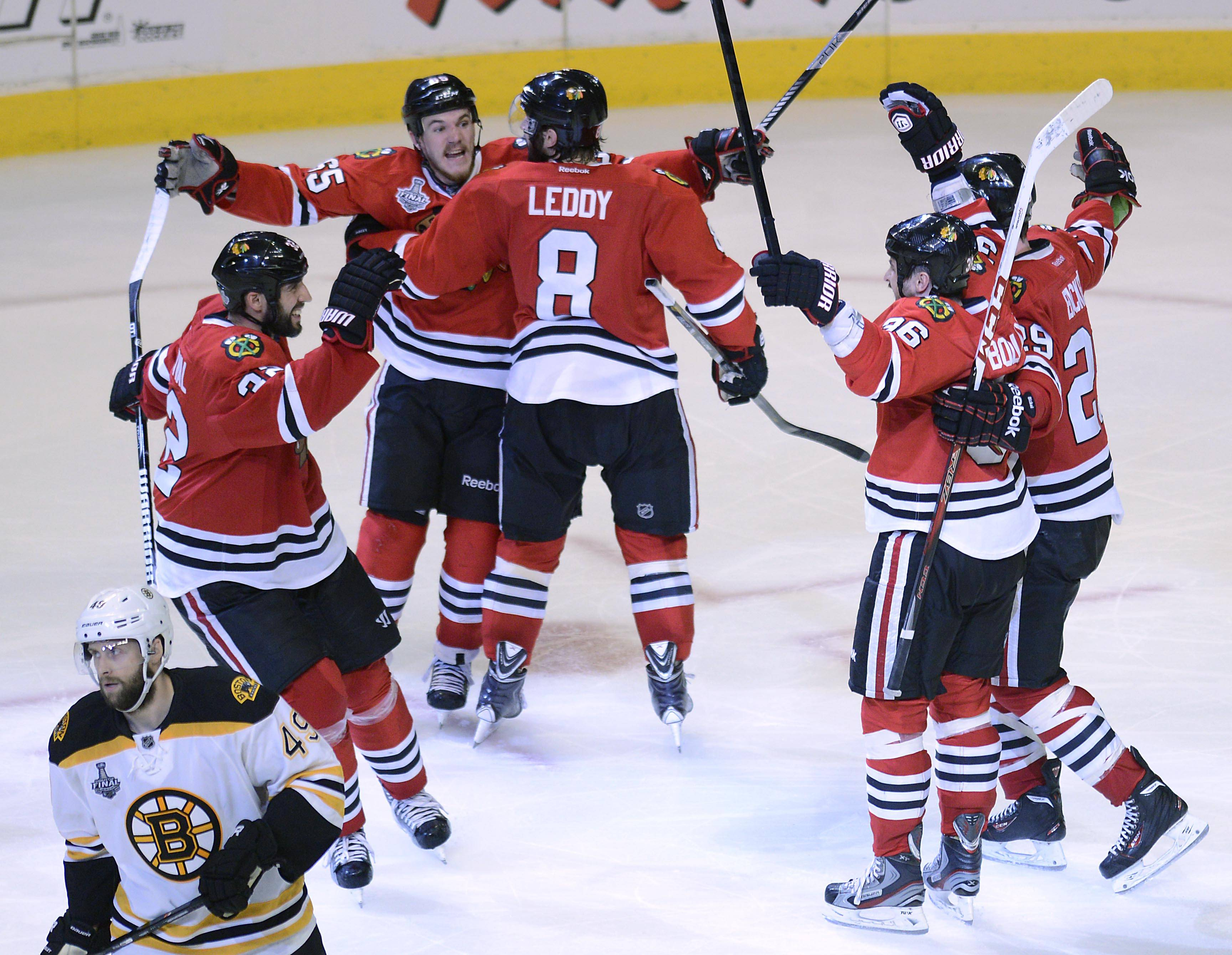 Chicago Blackhawks center Andrew Shaw is surrounded by teammates after his game-winning goal in the third overtime against the Boston Bruins during Game 1 of the Stanley Cup Finals Wednesday at the Untied Center in Chicago.