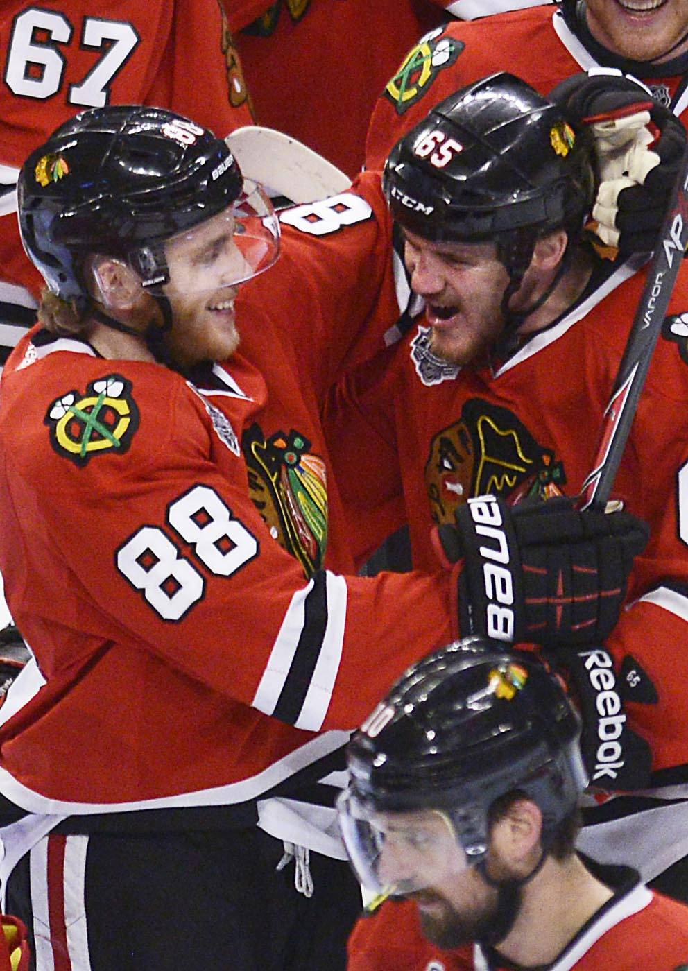 Chicago Blackhawks center Andrew Shaw is hugged by teammate Patrick Kane after his game winning goal in the third overtime of Game 1 of the Stanley Cup Finals Wednesday at the Untied Center in Chicago.