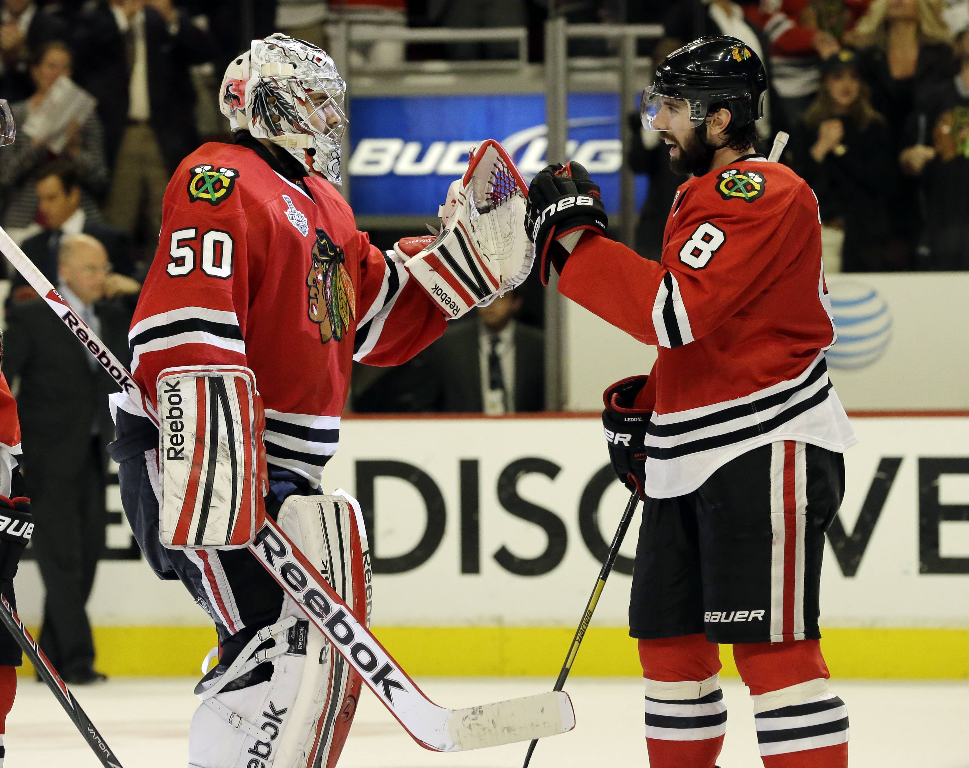 Chicago Blackhawks goalie Corey Crawford (50) celebrates with defenseman Nick Leddy (8) during the third overtime period of Game 1 in their NHL Stanley Cup Final hockey series, Thursday, June 13, 2013, in Chicago.