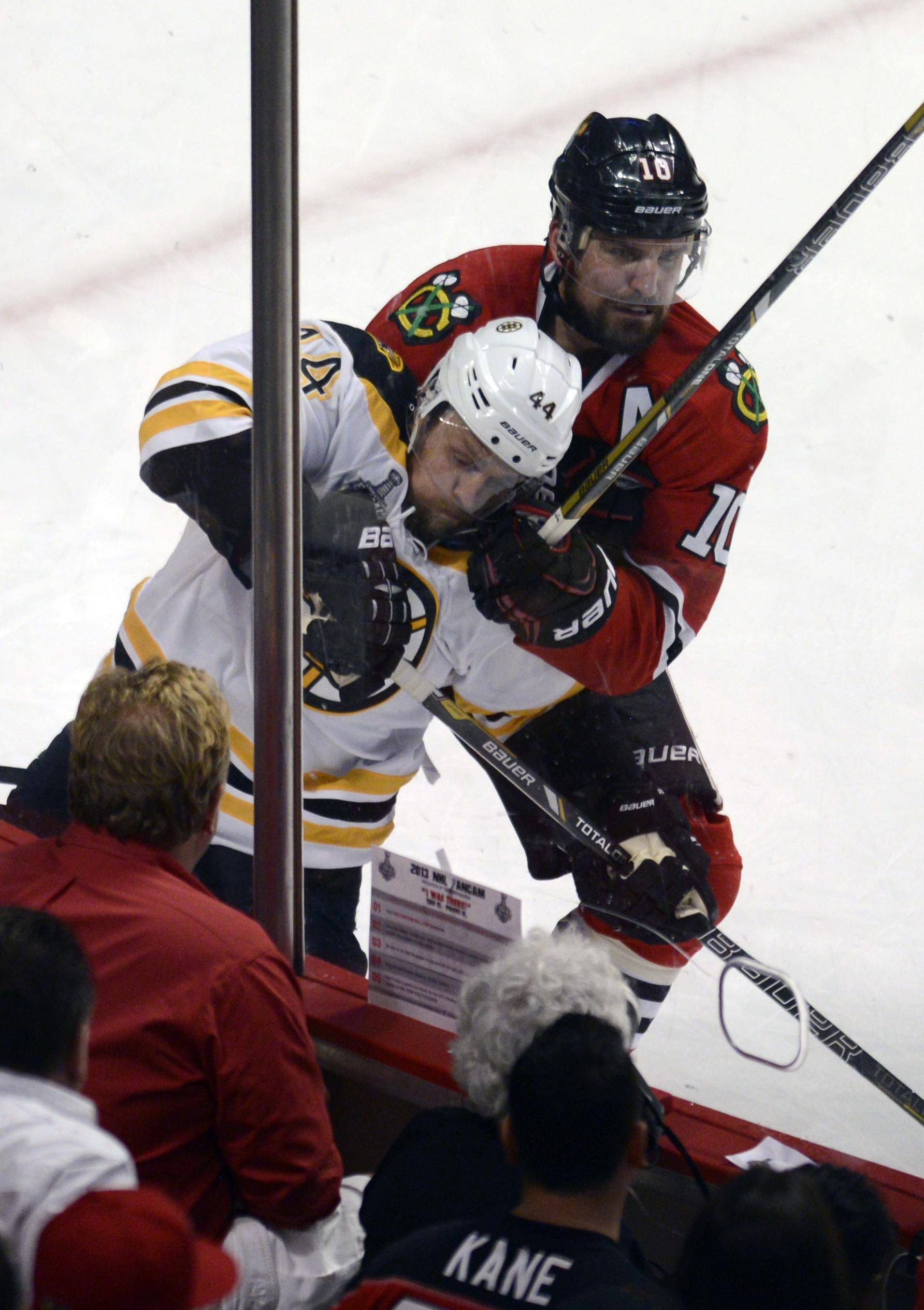 Chicago Blackhawks center Patrick Sharp and Boston Bruins defenseman Dennis Seidenberg fight on the boards in the third period during Game 1 of the Stanley Cup Finals Wednesday at the Untied Center in Chicago.