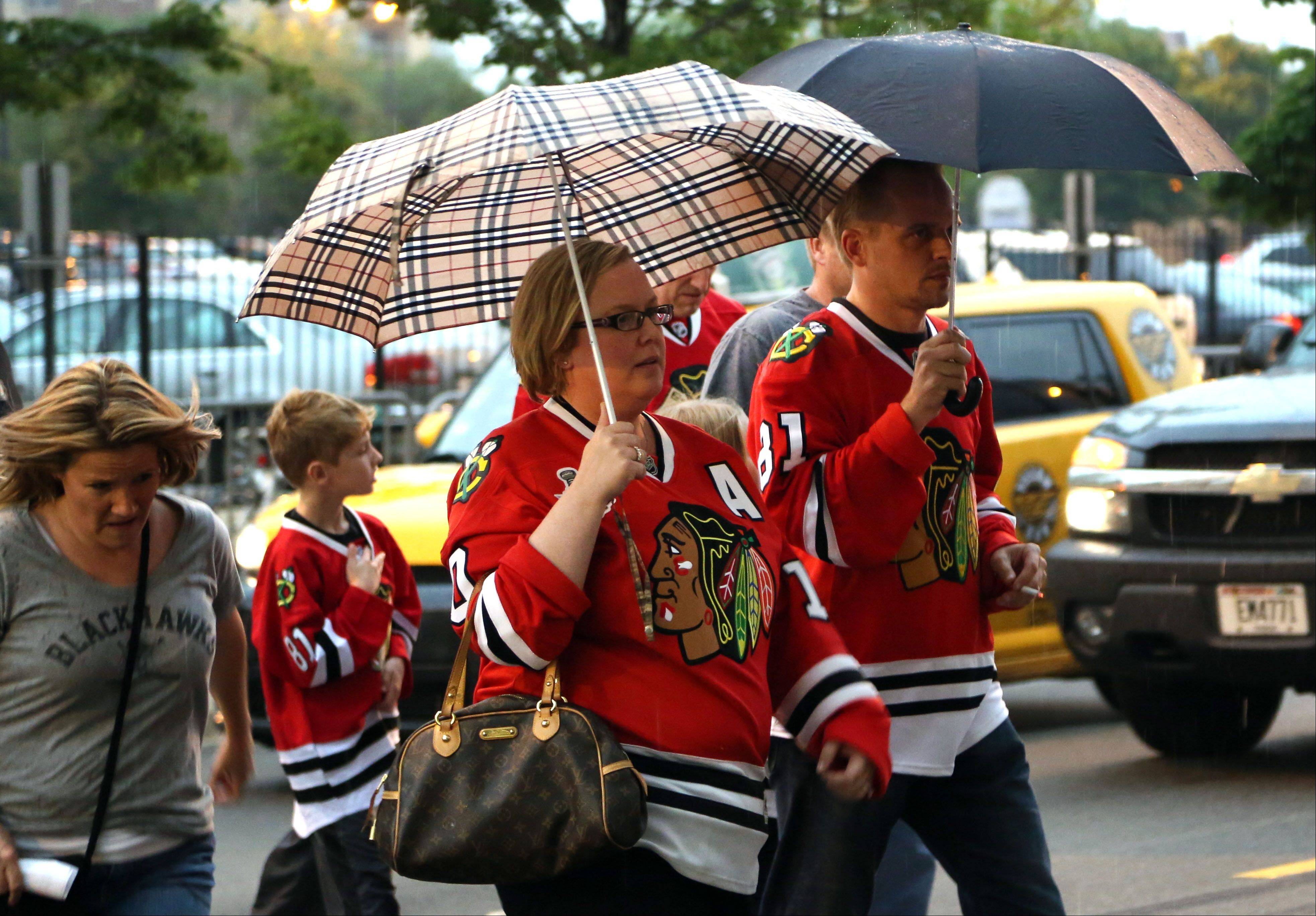 Blackhawks fans cover up as they make their way into the United Center.