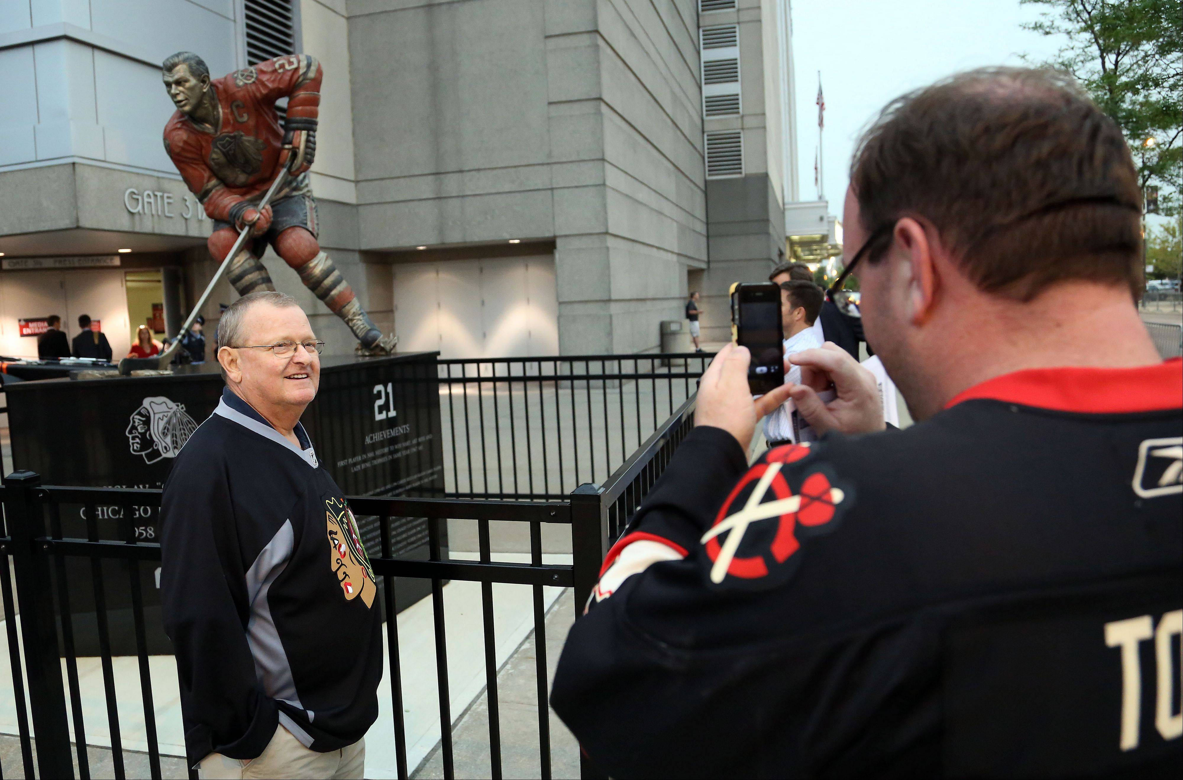 Bart Roberts of Elkhorn, Indiana shoots a picture of his father Larry in front of the Stan Mikita statue.