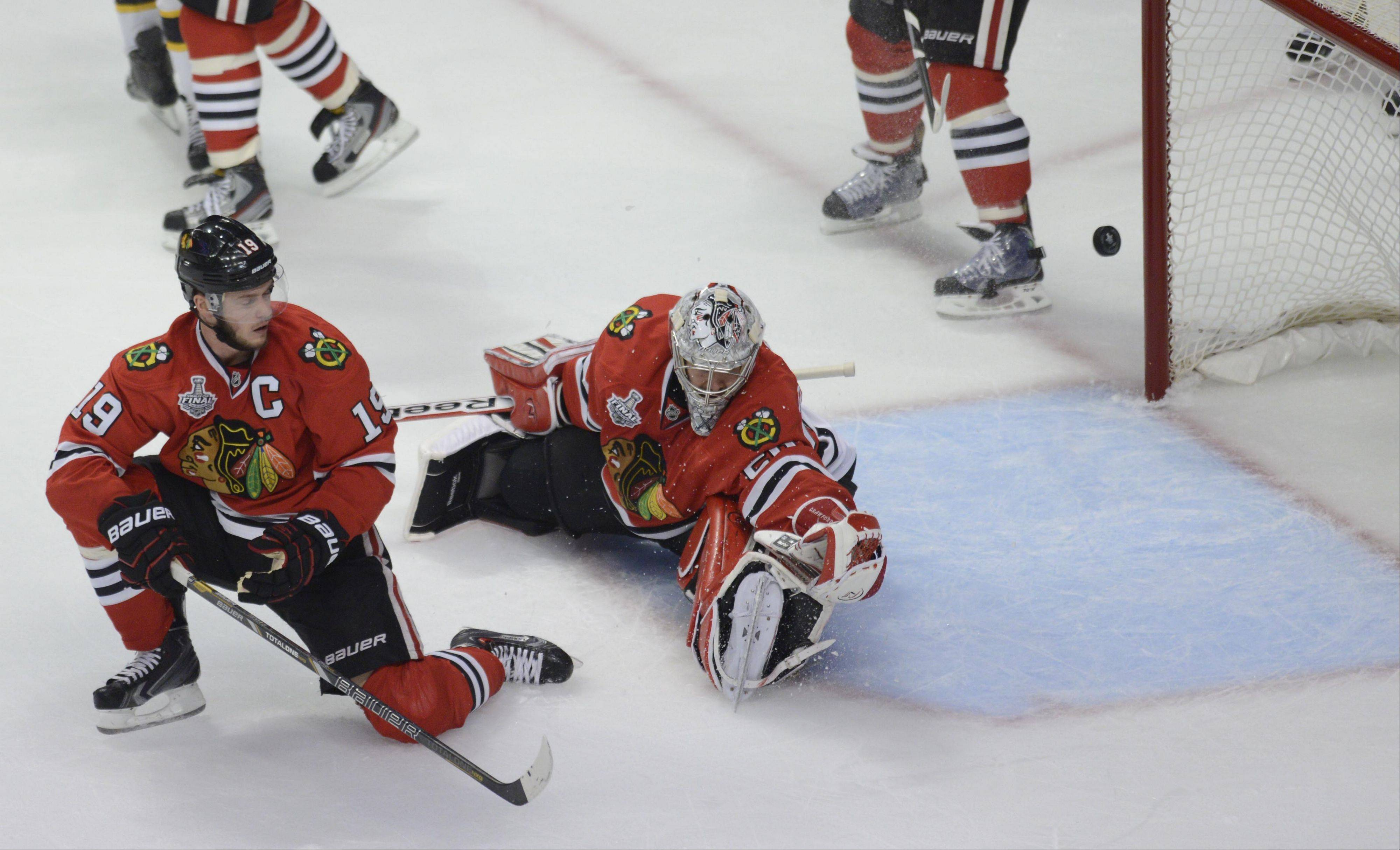 The puck gets past Chicago Blackhawks goalie Corey Crawford for the first goal by Milan Lucic of the Boston Bruins.
