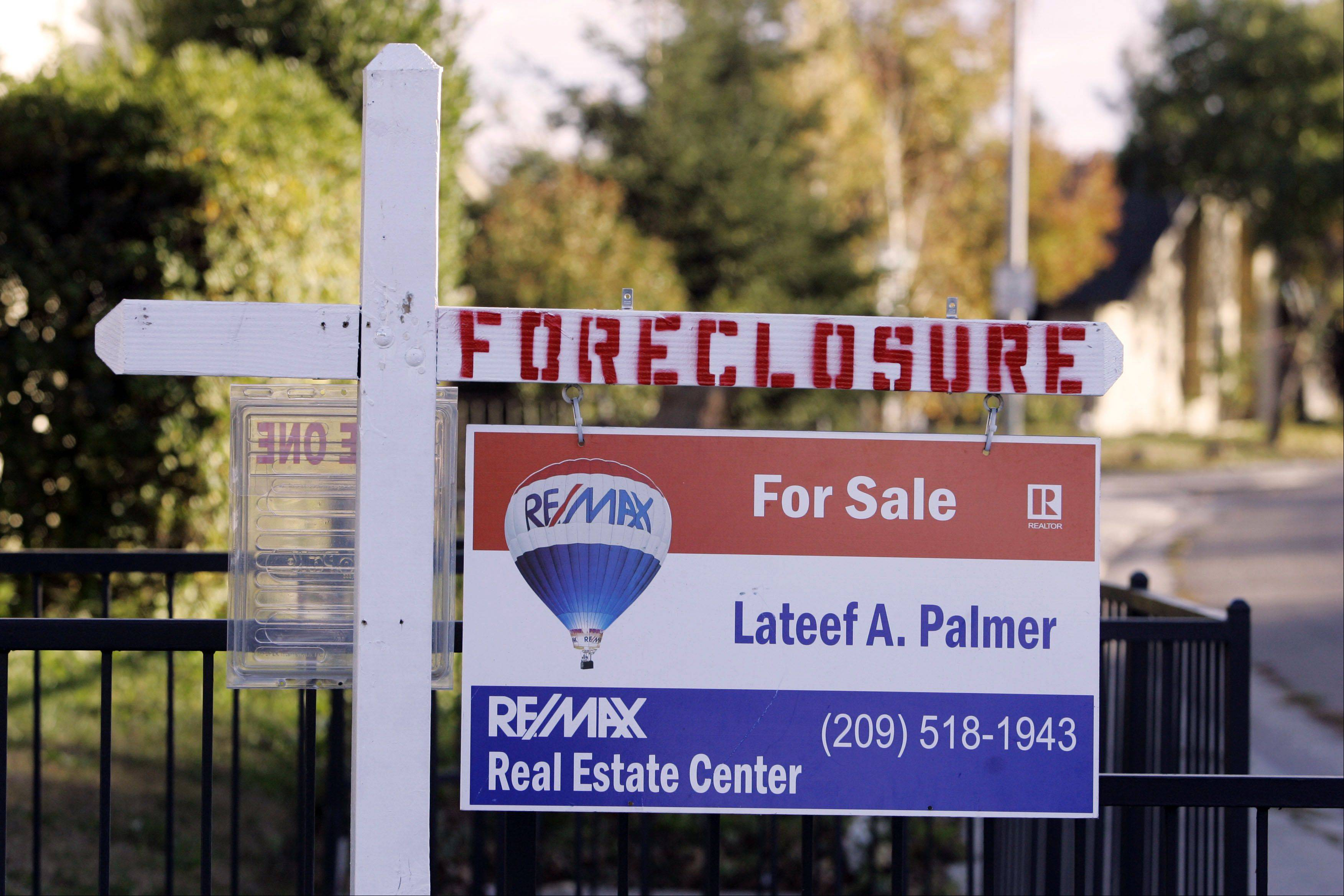 A foreclosure sign is seen atop a sale sign for a house in Stockton, Calif., Saturday, Dec. 1, 2007. Home foreclosures soared to an all-time high in the final quarter of last year and are likely to keep on rising, underscoring the suffering of distressed homeowners and the growing danger the housing meltdown poses for the economy. (AP Photo/Marcio Jose Sanchez)