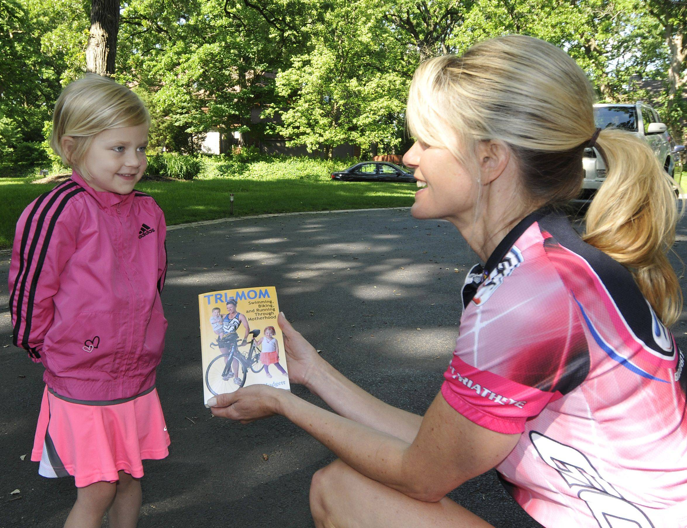 "Debra Hodgett of West Chicago, right, shows Molly Garrison, left, the cover of a new book, ""Tri-Mom: Swimming, Biking and Running Through Motherhood,"" about combining parenting with fitness. Molly was featured on the cover of the book."