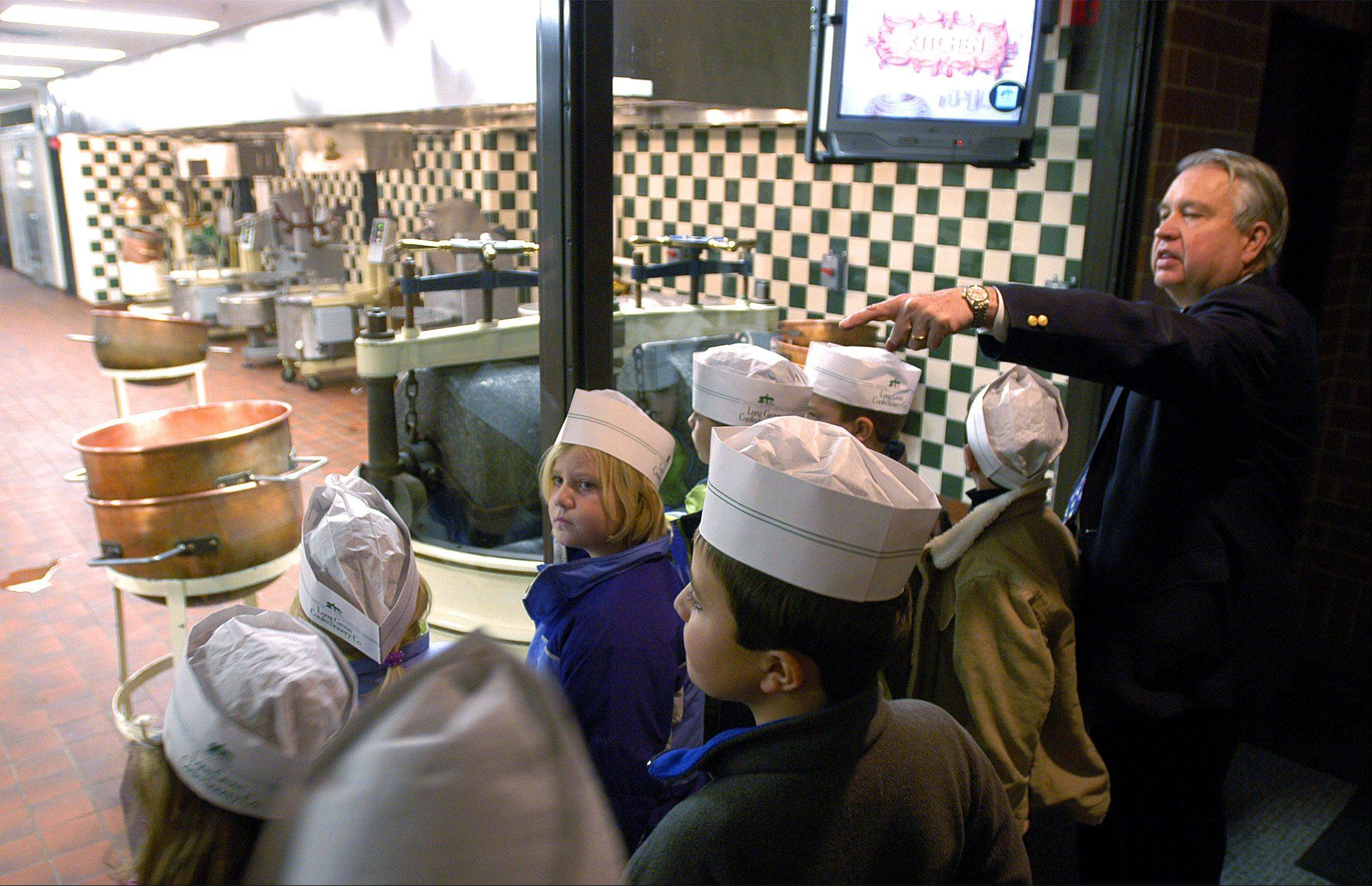 Long Grove Confectionery owner John Mangel shows students the kitchen area of his candy factory as they begin the tour of the company's new Buffalo Grove headquarters in December 2002.