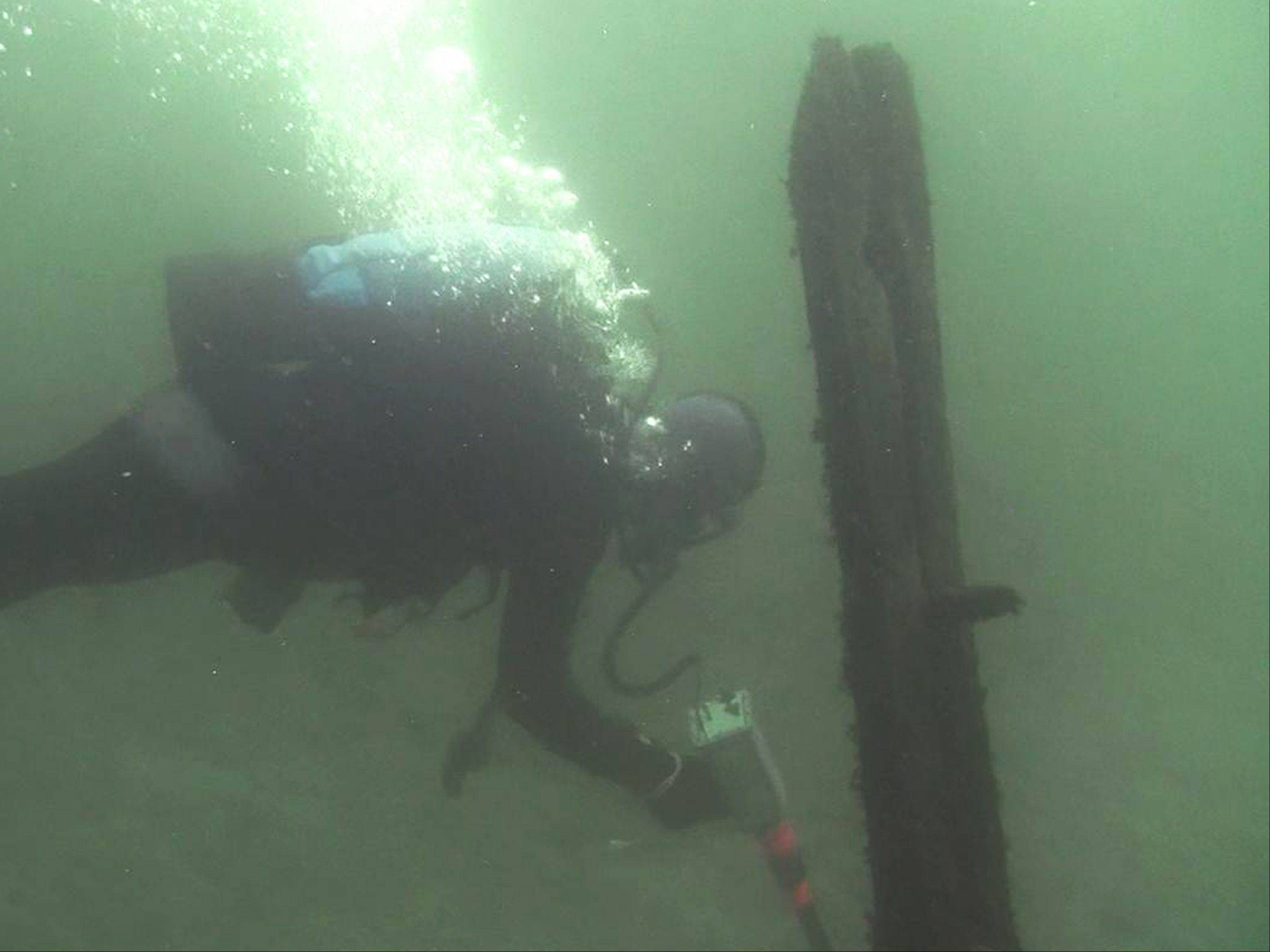 In October, diver Tom Kucharsky passes timbers protruding from the bottom of Lake Michigan that were discovered by Steve Libert in 2001.