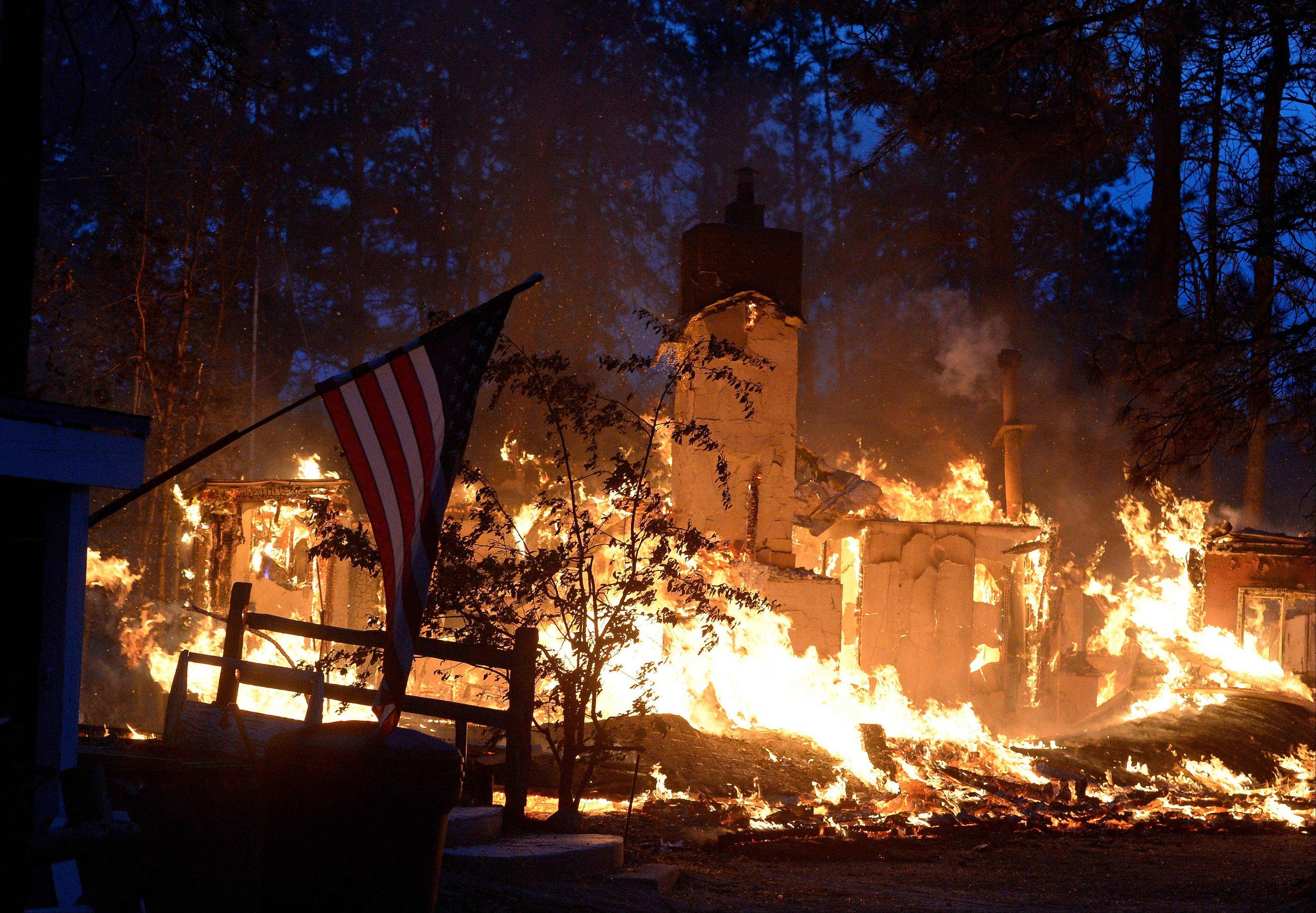 A house is fully engulfed in flames in the midst of the Black Forest Fire northeast of Colorado Springs on Wednesday, June 12, 2013.