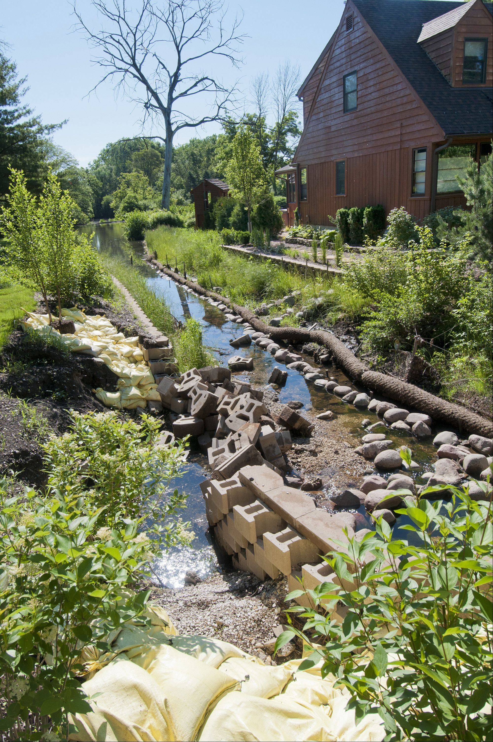 Part of the retaining wall on a channel that connects Glen Ellyn�s stormsewer system with Perry�s Pond is now a pile of rubble after April storms damaged stabilization improvements that had been made.