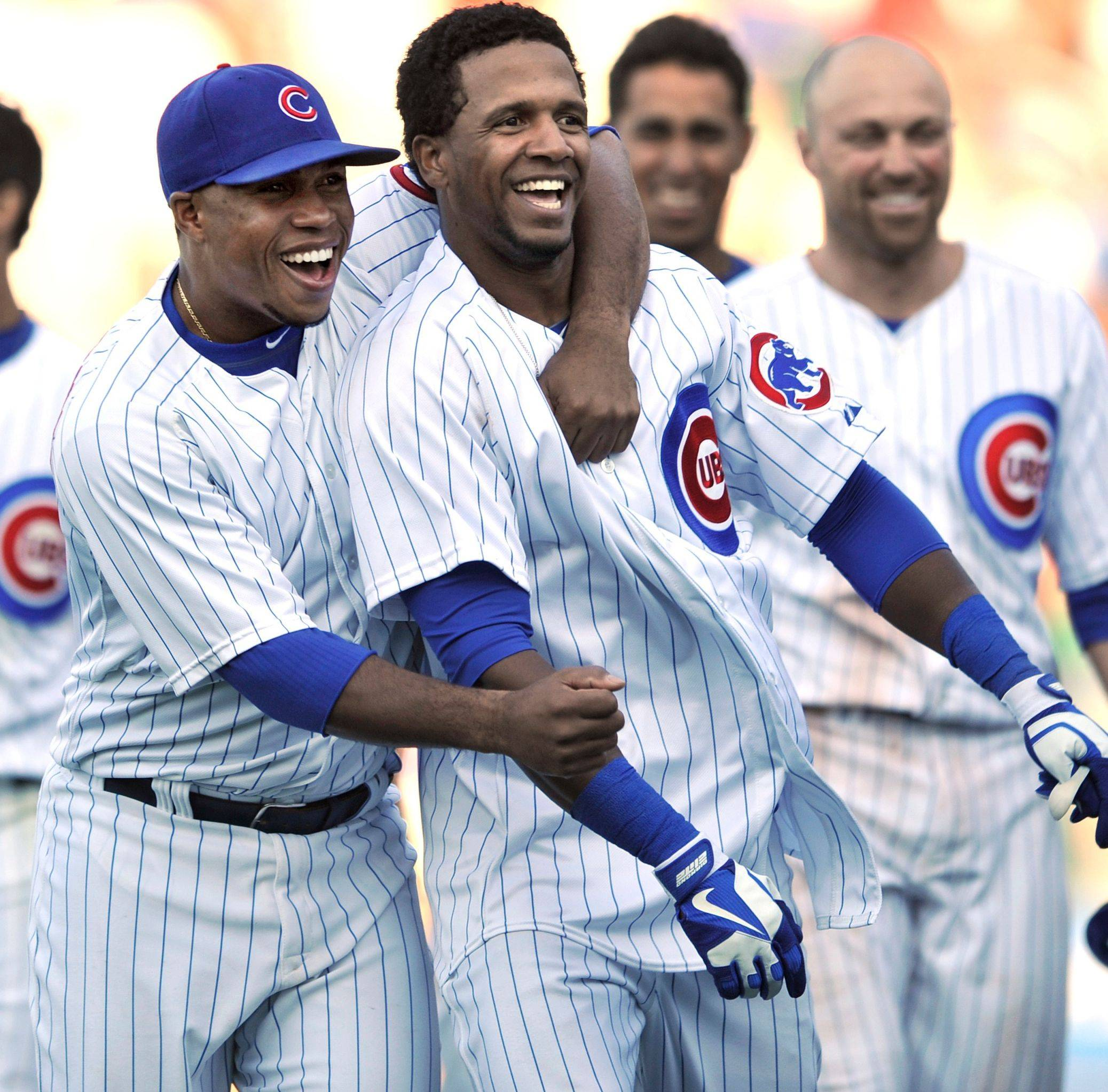 Julio Borbon, front right, celebrates with teammate Luis Valbuena, left, after hitting a walkoff-single to defeat the Reds on Thursday at Wrigley Field.
