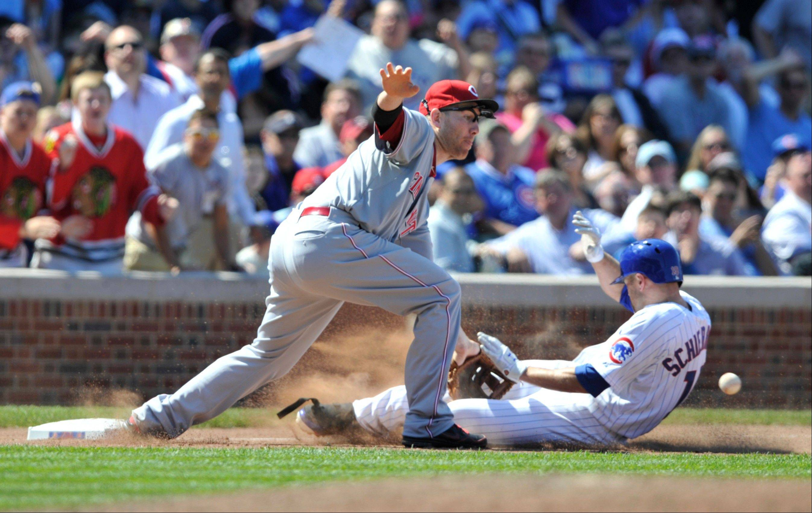 The Cubs' Nate Schierholtz, right, slides safely into third as Cincinnati Reds' Todd Frazier waits for the ball after hitting a triple during the sixth inning of a baseball game on Thursday at Wrigley Field.