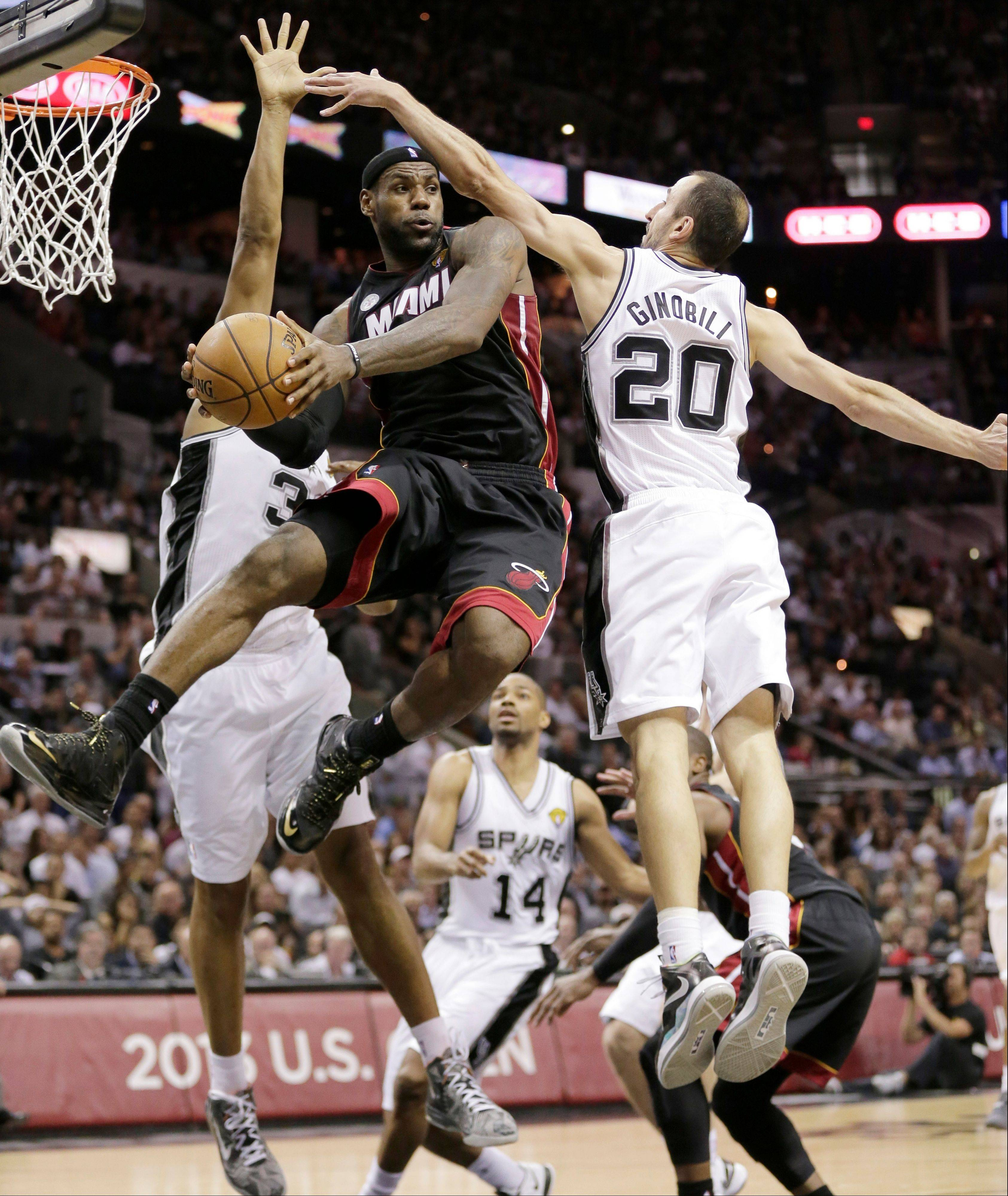 Miami Heat's LeBron James (6) passes between San Antonio Spurs' Boris Diaw (33), of France, and Manu Ginobili (20) during the second half at Game 4 of the NBA Finals basketball series Thursday in San Antonio.