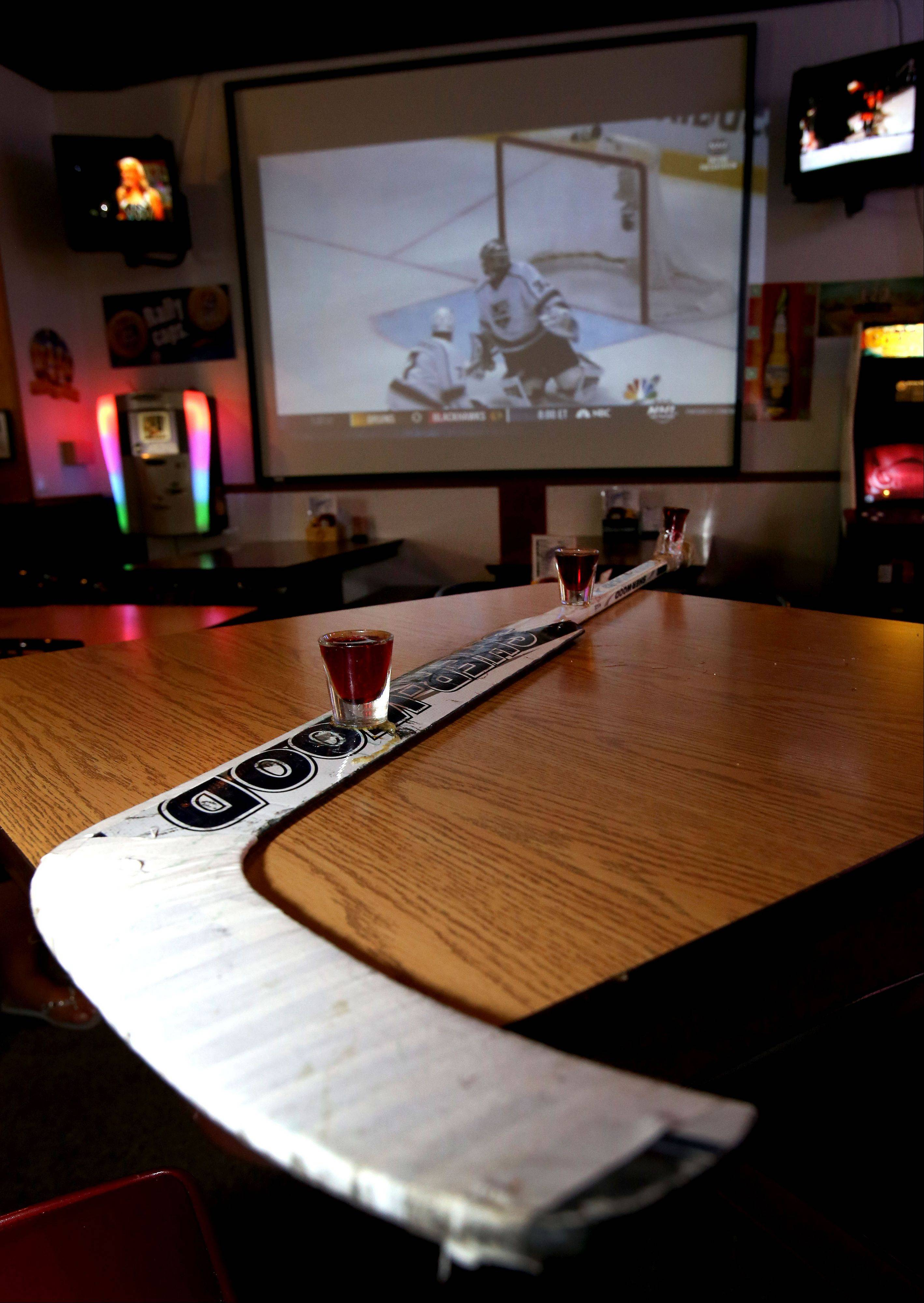 Fans can do shots from a hockey stick during the game at Blue Line Bar & Grill in Addison.