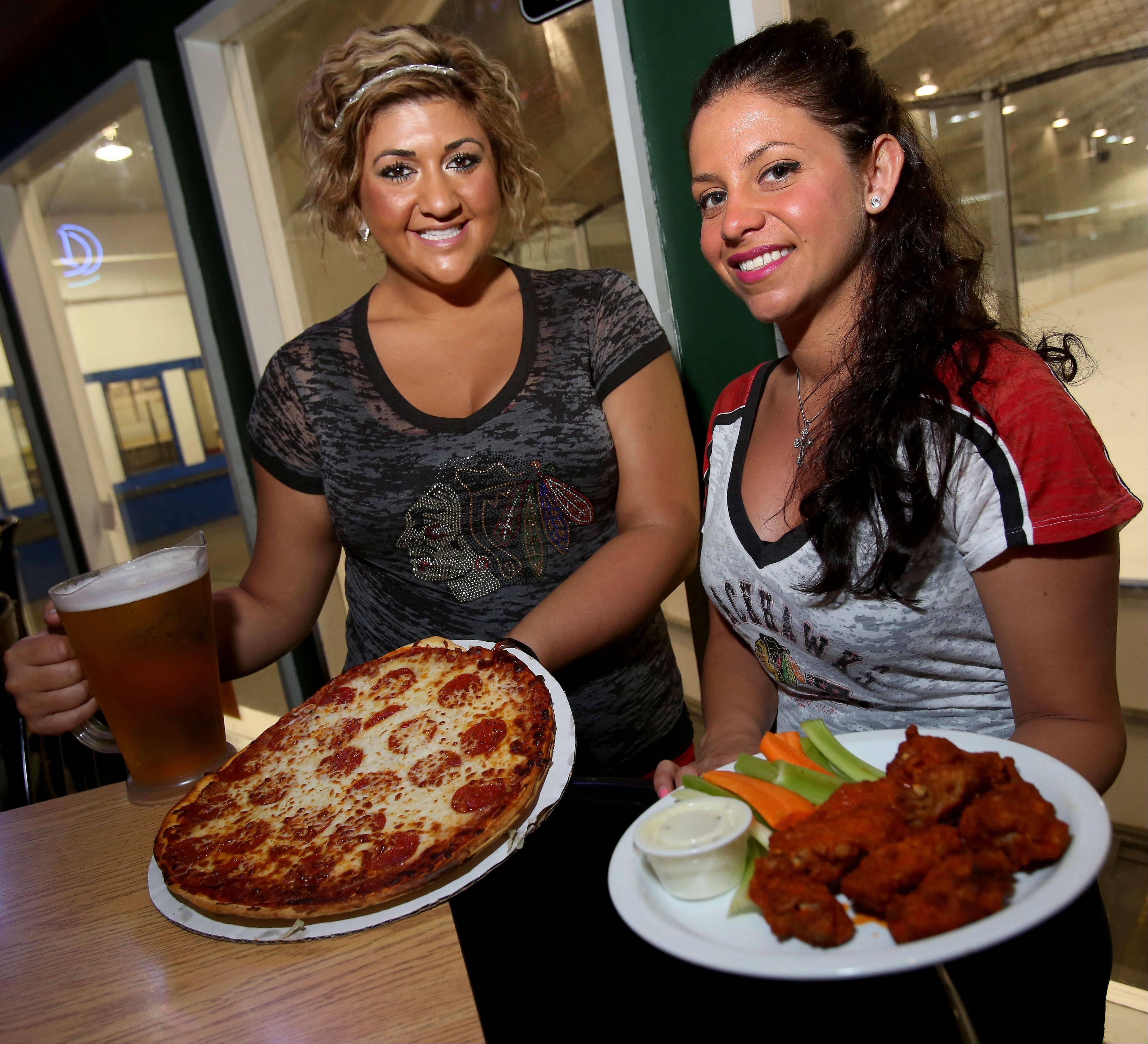 Hawks fans can enjoy pizza, beer and wings served up by Dani D'Ambrose, left, and Jessica Larsen at the Blue Line Bar & Grill in Addison.
