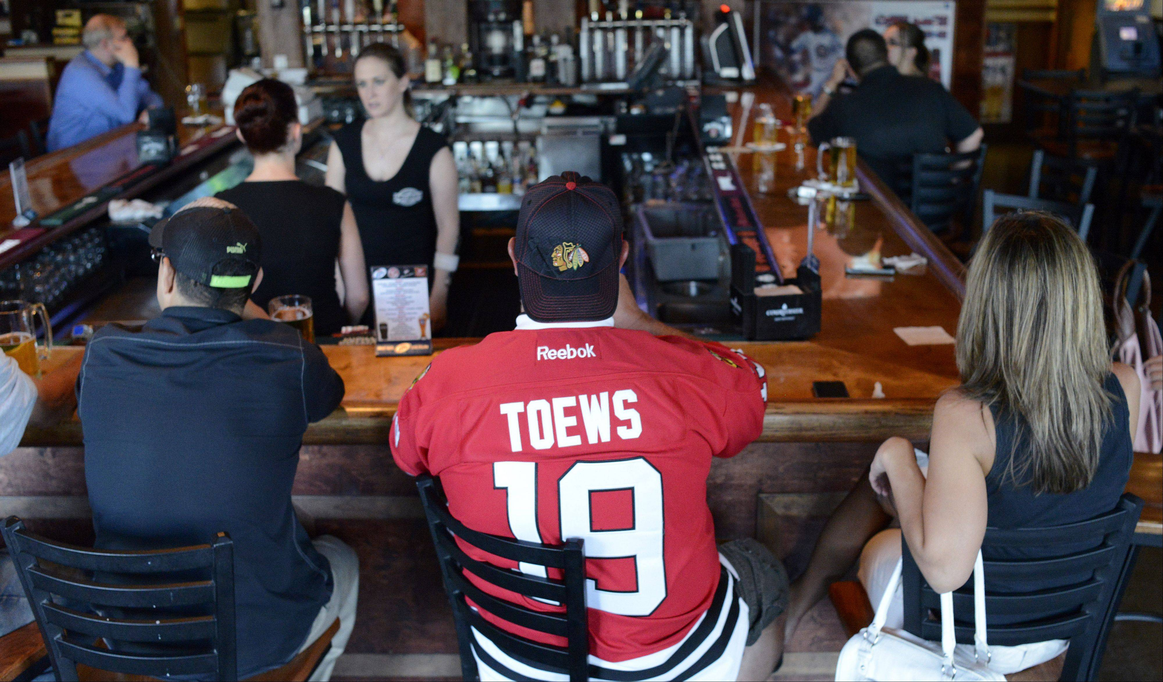 Regular customer Scott Kennedy of Aurora wears his Jonathan Toews jersey while sitting with wife Kim at Chelios' Pub in Aurora.