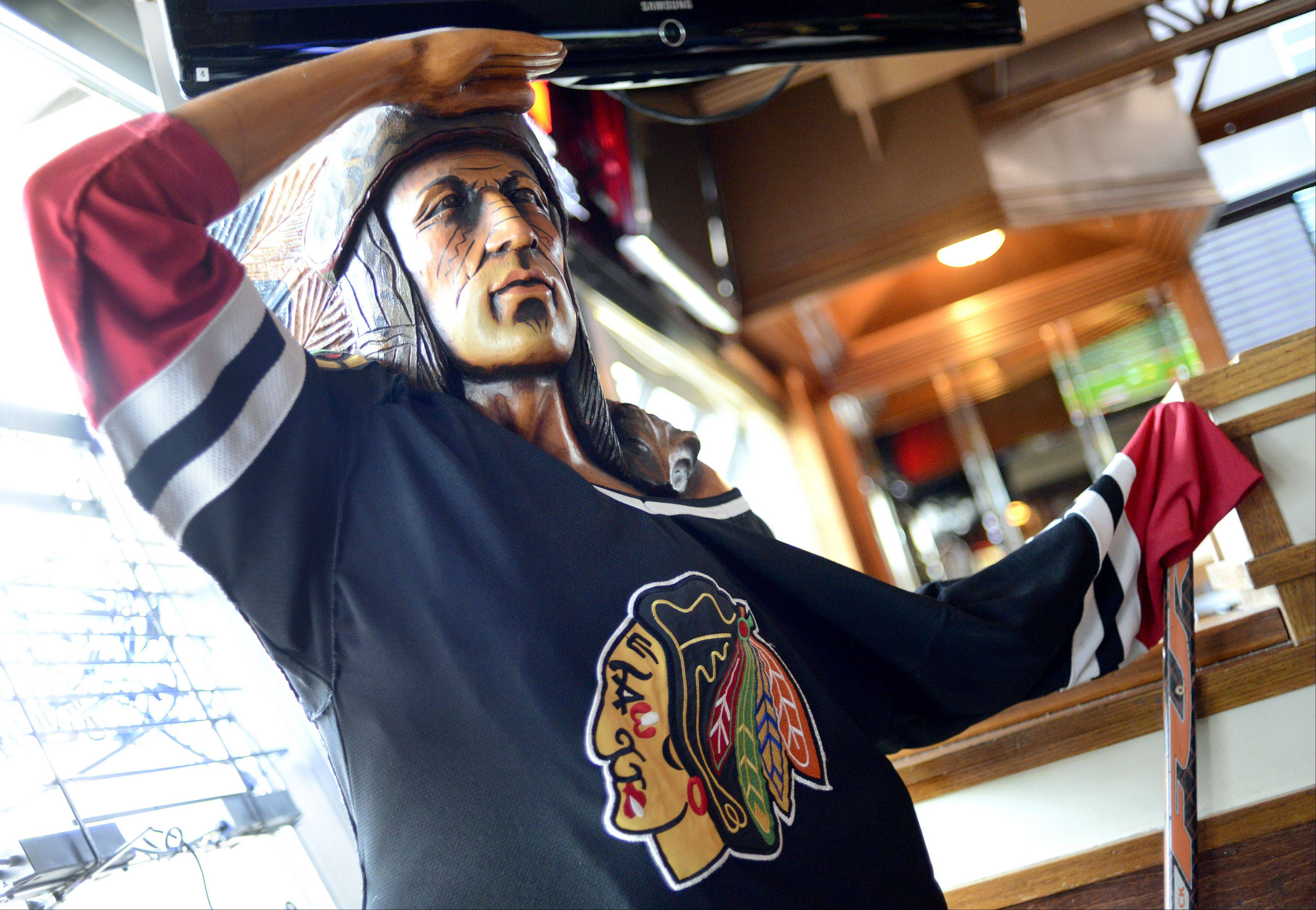 A chief wears the official Chicago Blackhawks jersey, with hockey stick in hand, at Chelios' Pub in Aurora.