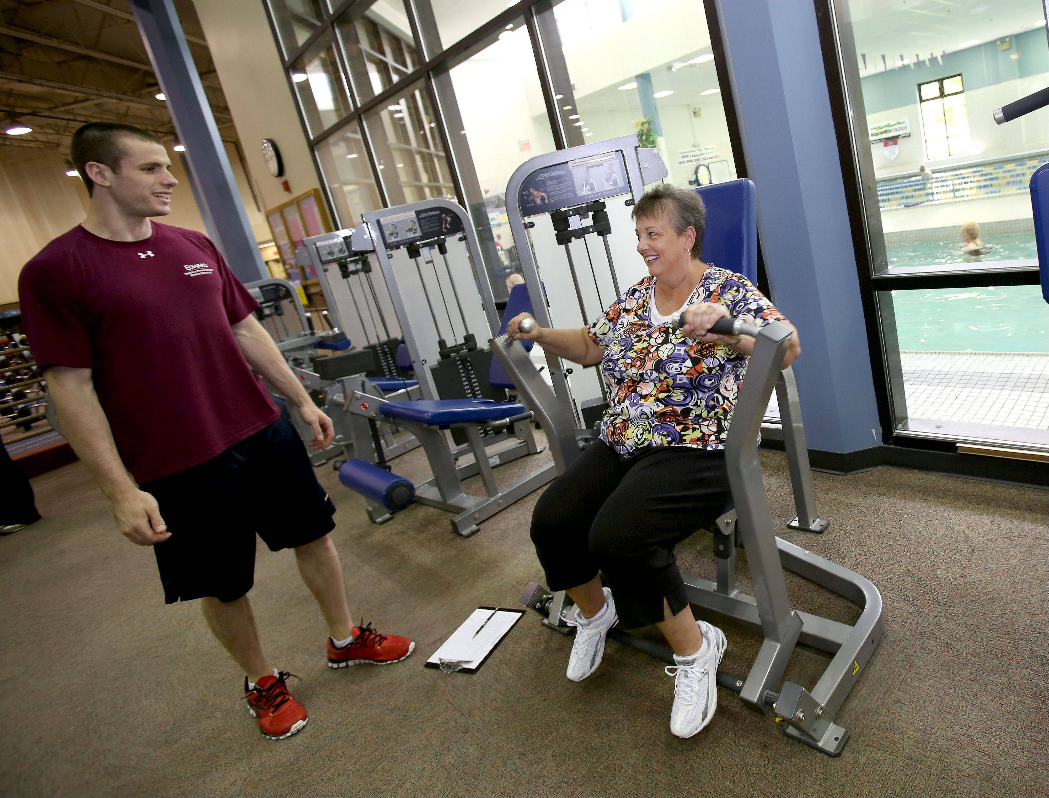 Fitness Specialist Steve Finn shows new member Patty Macko of Naperville the proper technique for using the machines at the Edward Health & Fitness Center at Edward Hospital.