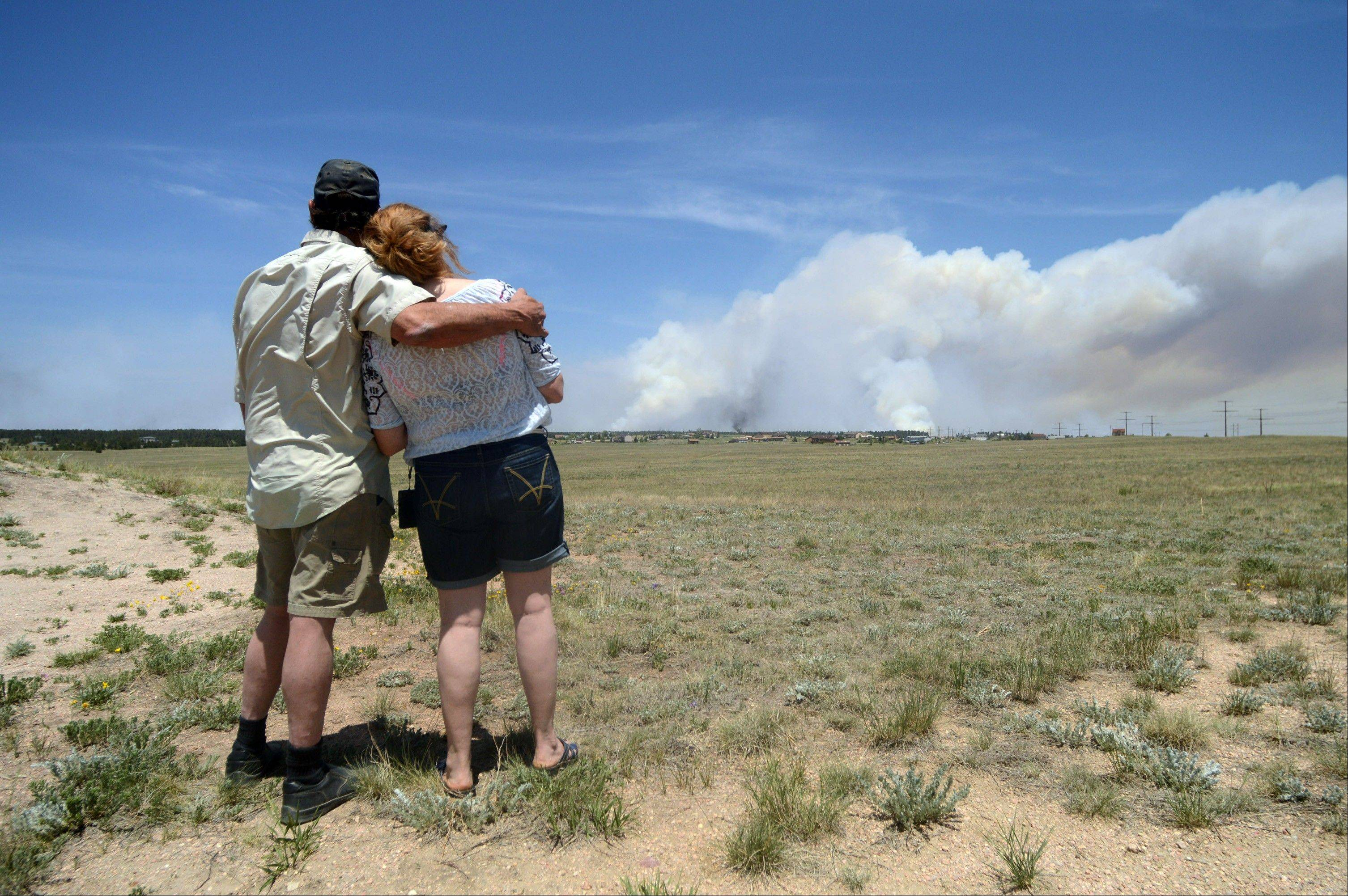 Dave and Linda Burgess watch as a plume rises near their home on Burgess Road in The Black Forest on Wednesday, June 12, 2013 near Colorado Springs, Colo. They were not sure if their home survived the fire.