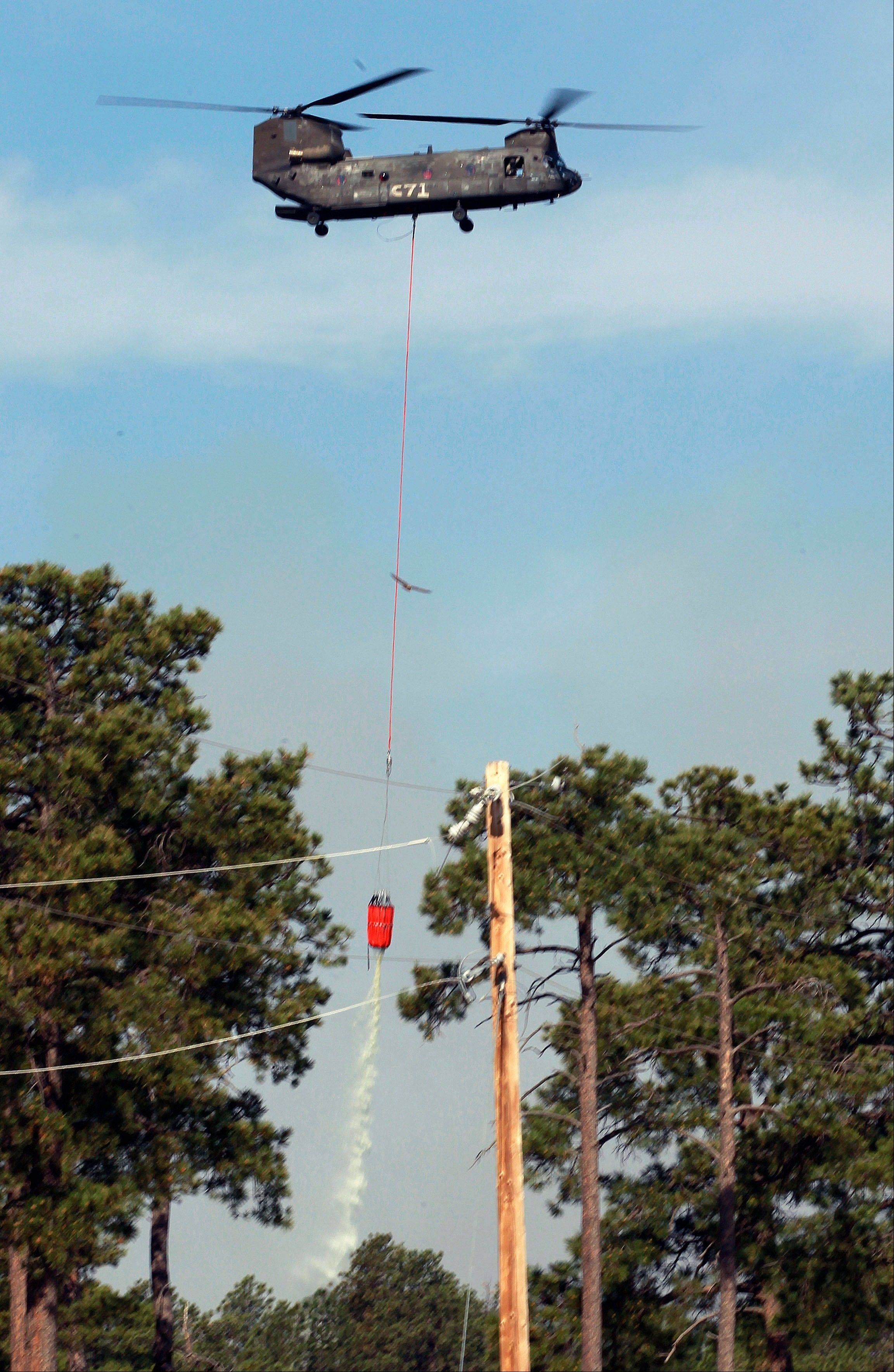 A U.S. Army Chinook helicopter drops a load of water on the Black Forest wildfire, north of Colorado Springs, Colo., on Thursday, June 13, 2013.