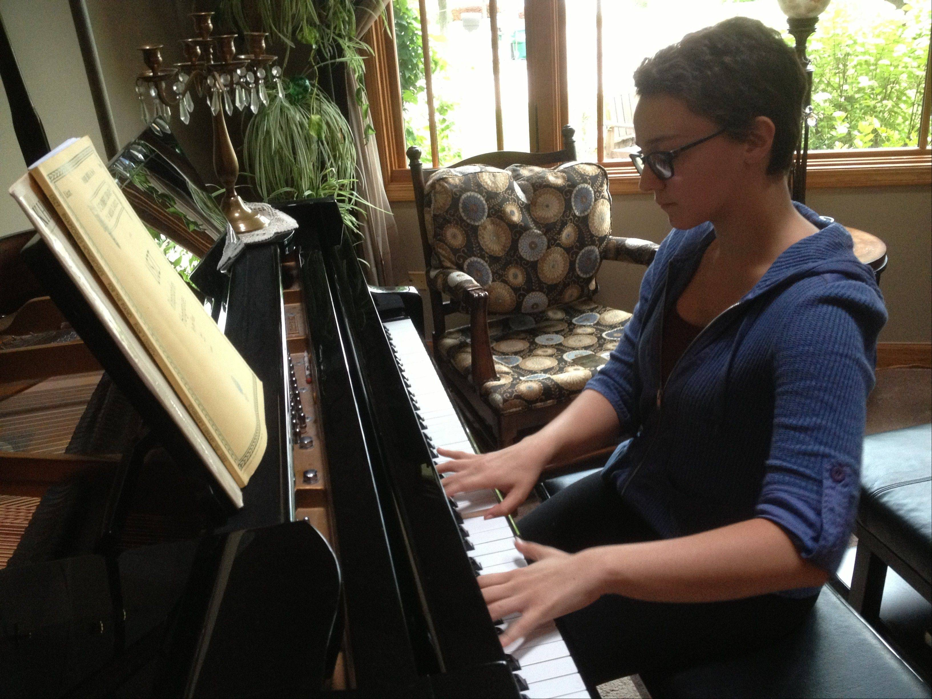 Chelsie Coren plays a piece on the grand piano in her home.
