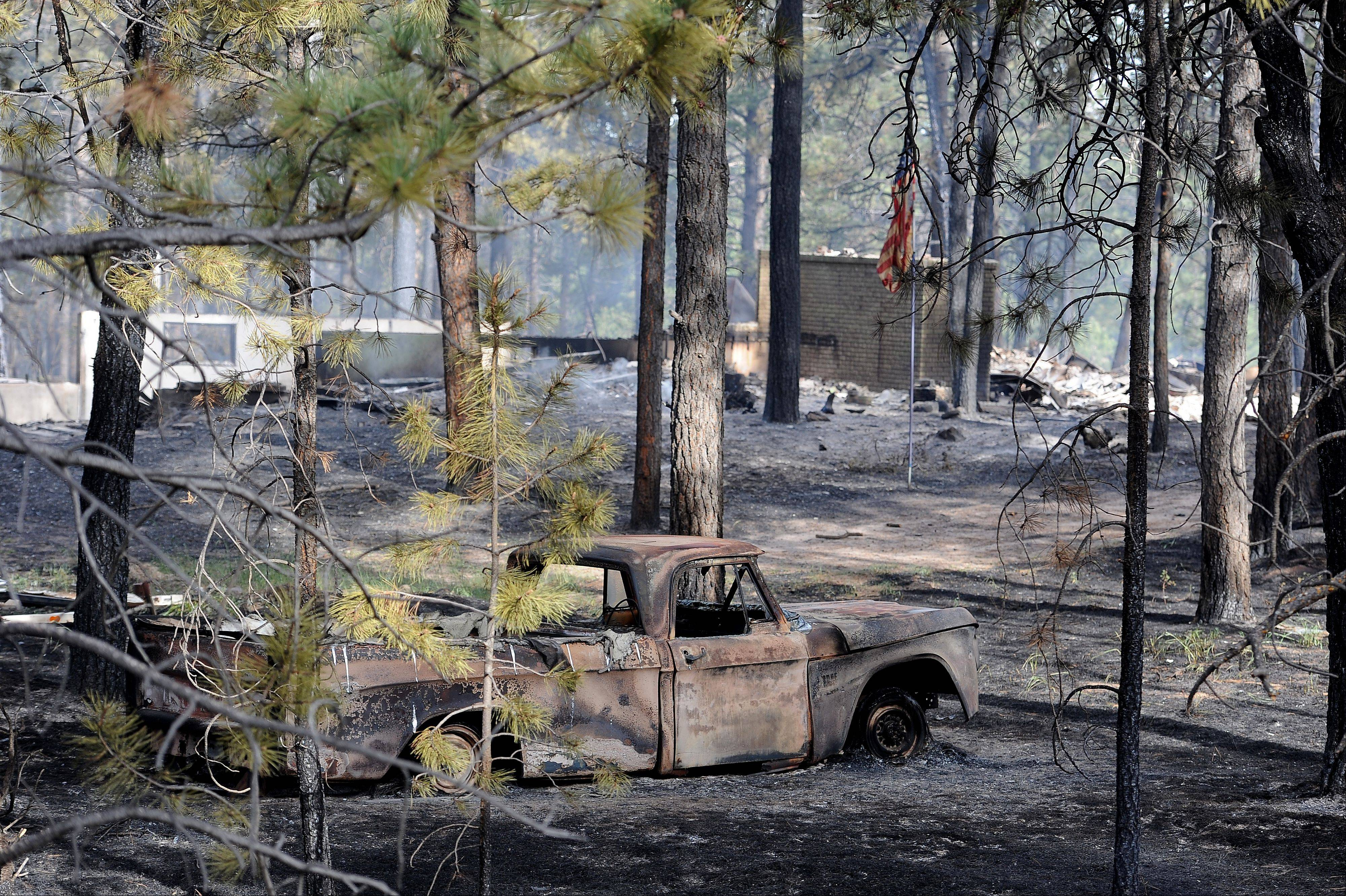 Blackened and charred homes are left along Herring Road in the Black Forest area northeast of Colorado Springs, Colo., on Wednesday, June 12, 2013. The Black Forest Fire northeast of Colorado Springs earlier prompted evacuation orders and pre-evacuation notices to more than 9,000 people and to about 3,500 homes and businesses, sheriff's officials said. The fire has destroyed more than 360 homes.