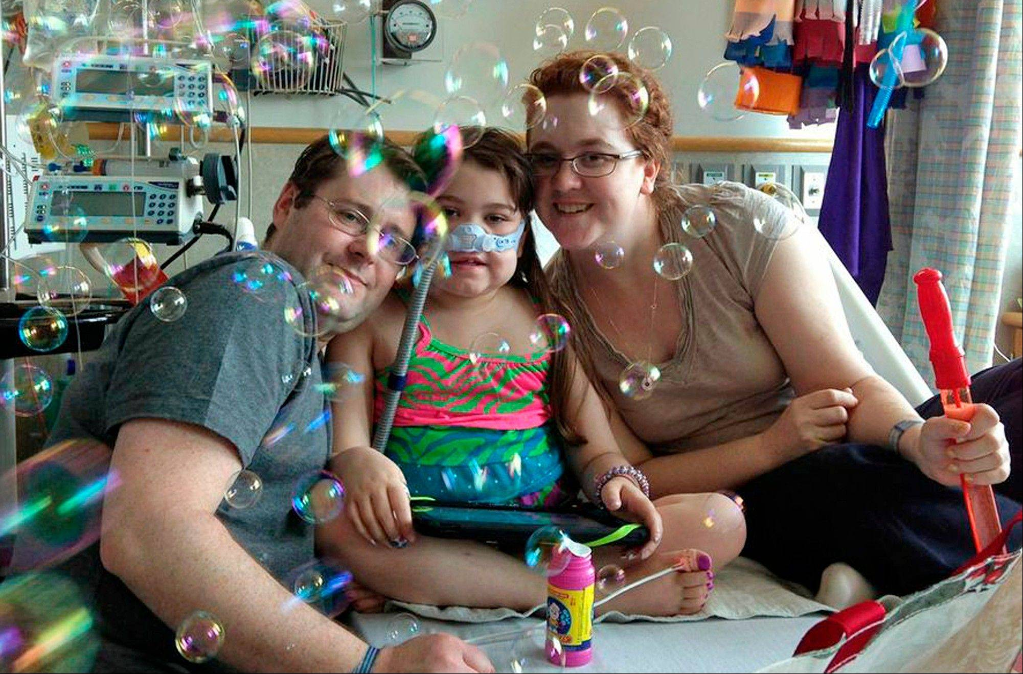 Sarah Murnaghan, center, celebrates the 100th day of her stay in Children's Hospital of Philadelphia with her father, Fran, left, and mother, Janet. The 10-year-old suburban Philadelphia girl received a lung transplant there Wednesday, June 12, 2013, her family said.