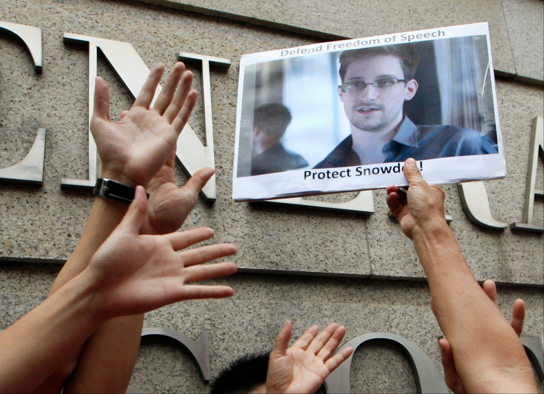 A supporter holds a picture of Edward Snowden, a former CIA employee who leaked top-secret information about U.S. surveillance programs, outside the U.S. Consulate General in Hong Kong Thursday, June 13, 2013.