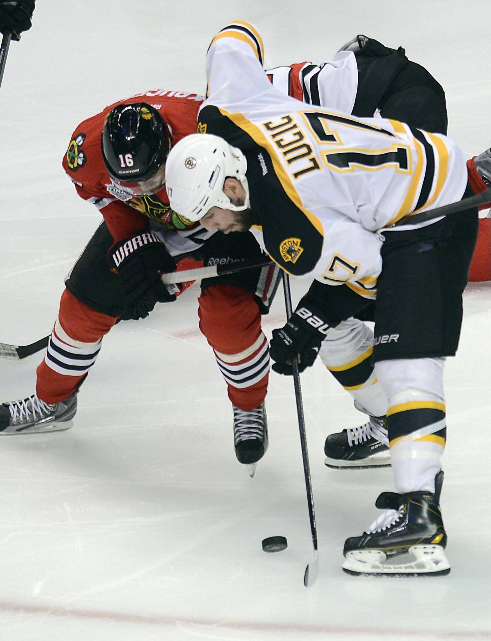 John Starks/jstarks@dailyherald.comBoston Bruins left wing Milan Lucic andChicago Blackhawks center Marcus Kruger battle for the puck in the third period during Game 1 of the Stanley Cup Finals Wednesday at the Untied Center in Chicago.