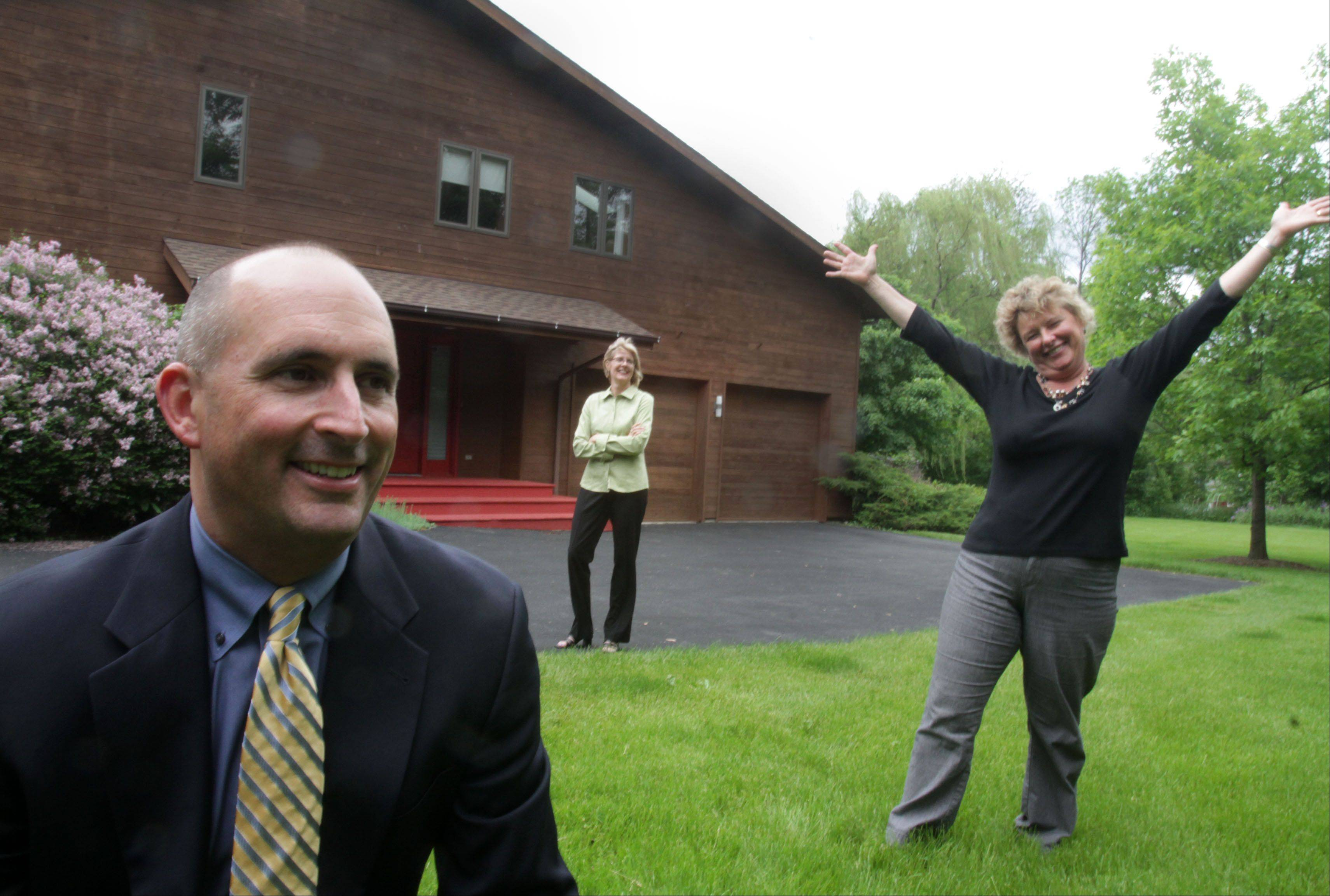 Realtor Mark Munro, left, former homeowner Irisa Putnins, right, and Mary Loughman, the stager, background, outside Putnins former home in Deer Park that they improved and sold in one day last year.