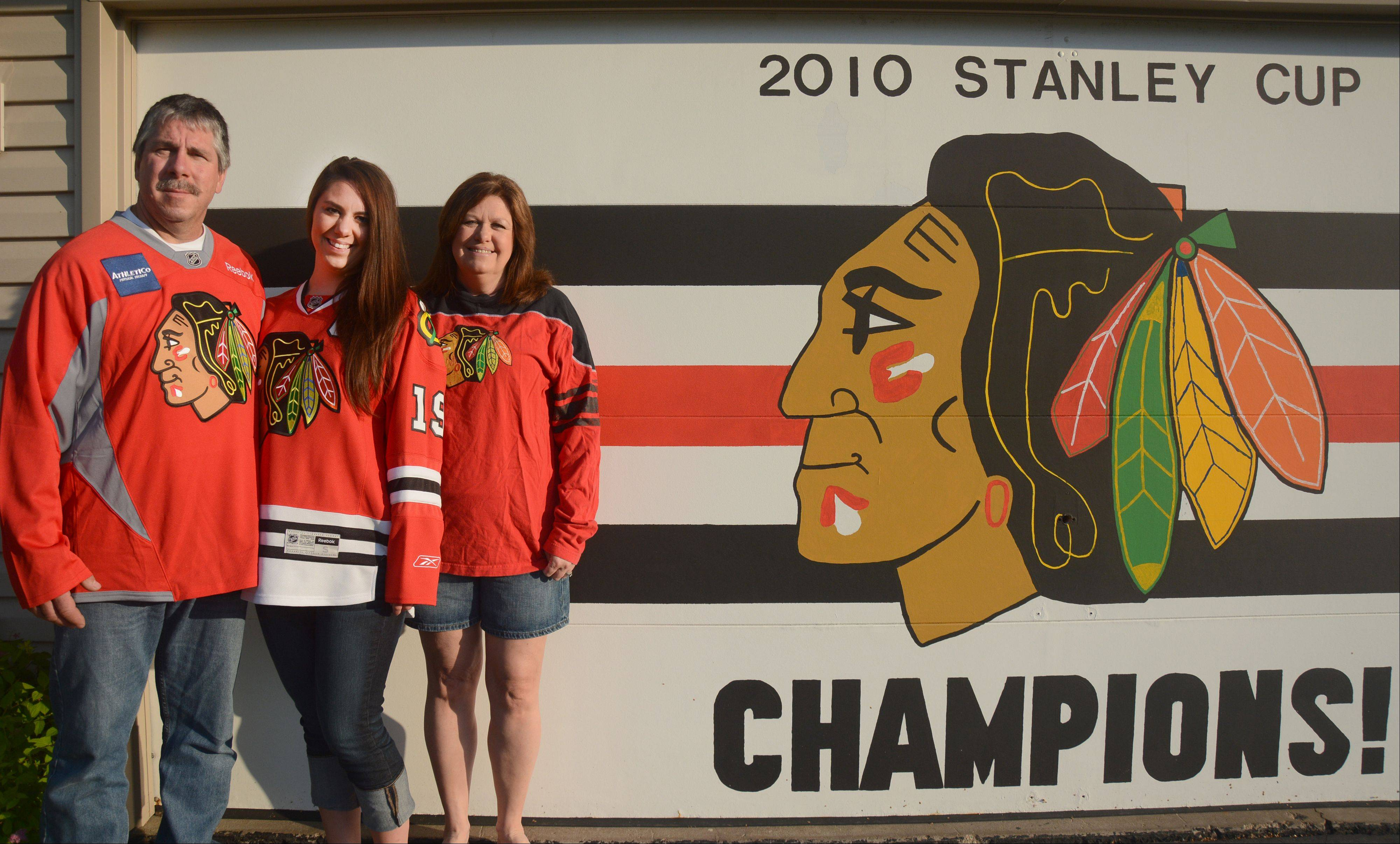"Rick Maher, daughter Allison and wife Mary hope to update the Hawks logo they painted on the garage of their Roselle home — with a ""2013"" entry."