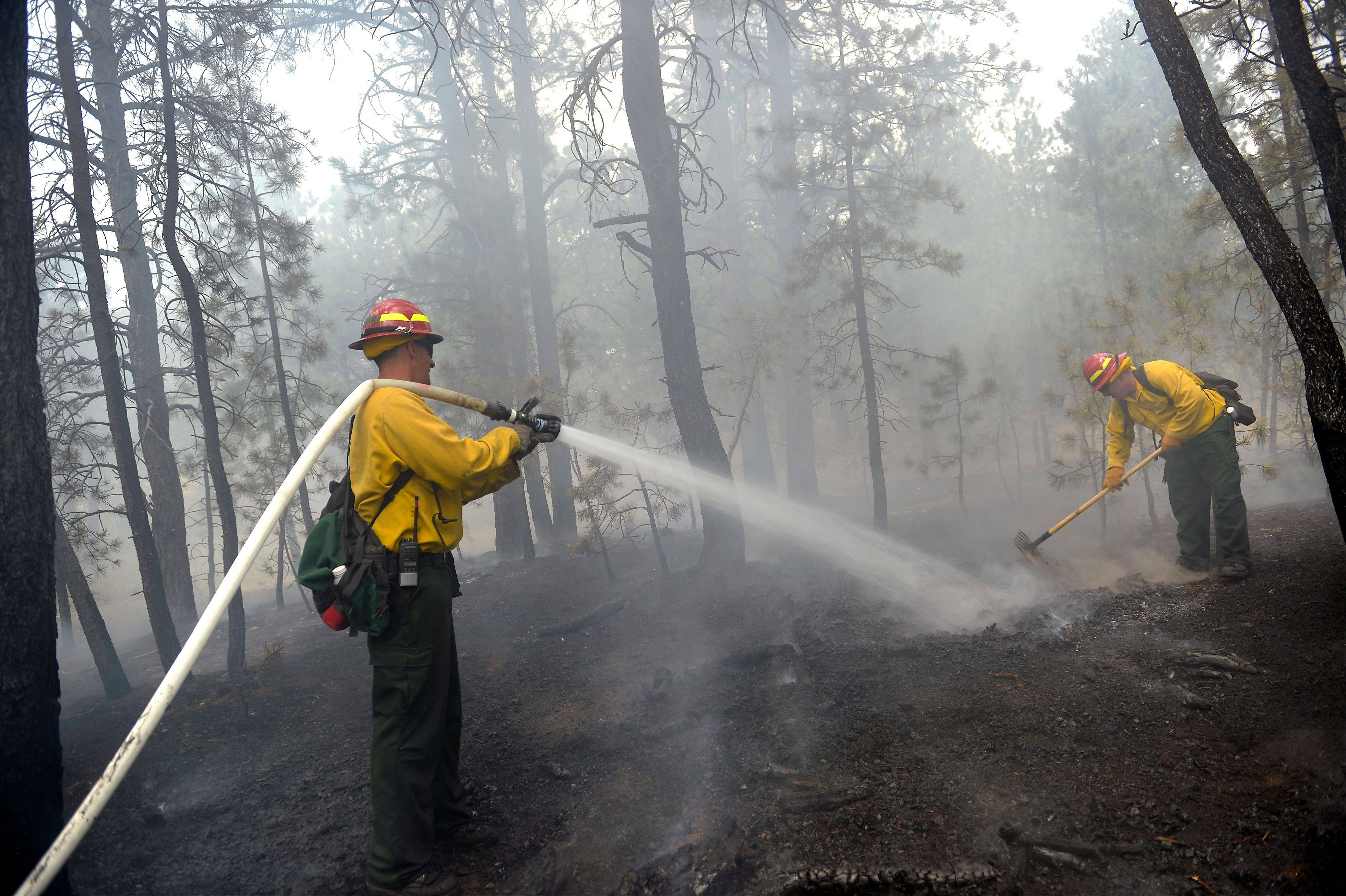 "Firefighters have at least temporarily battled to a ""draw"" with a fast-moving fire that already has killed two people and destroyed 379 homes, giving weary authorities and residents the first glimmer of hope after three days of mounting damage, a sheriff said."