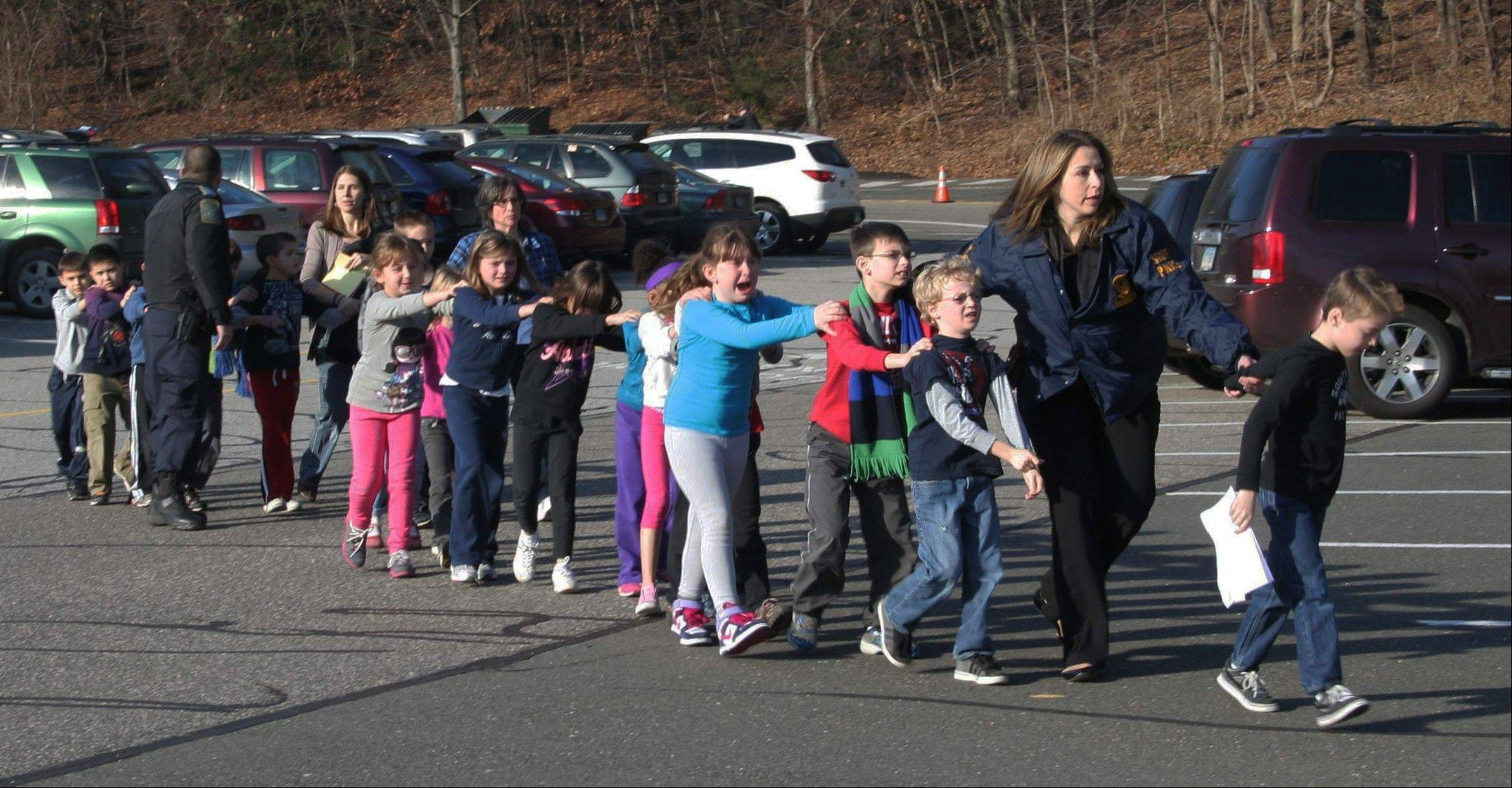 In this Friday, Dec. 14 photo Connecticut State Police lead a line of children from the Sandy Hook Elementary School in Newtown, Conn. after a shooting at the school.