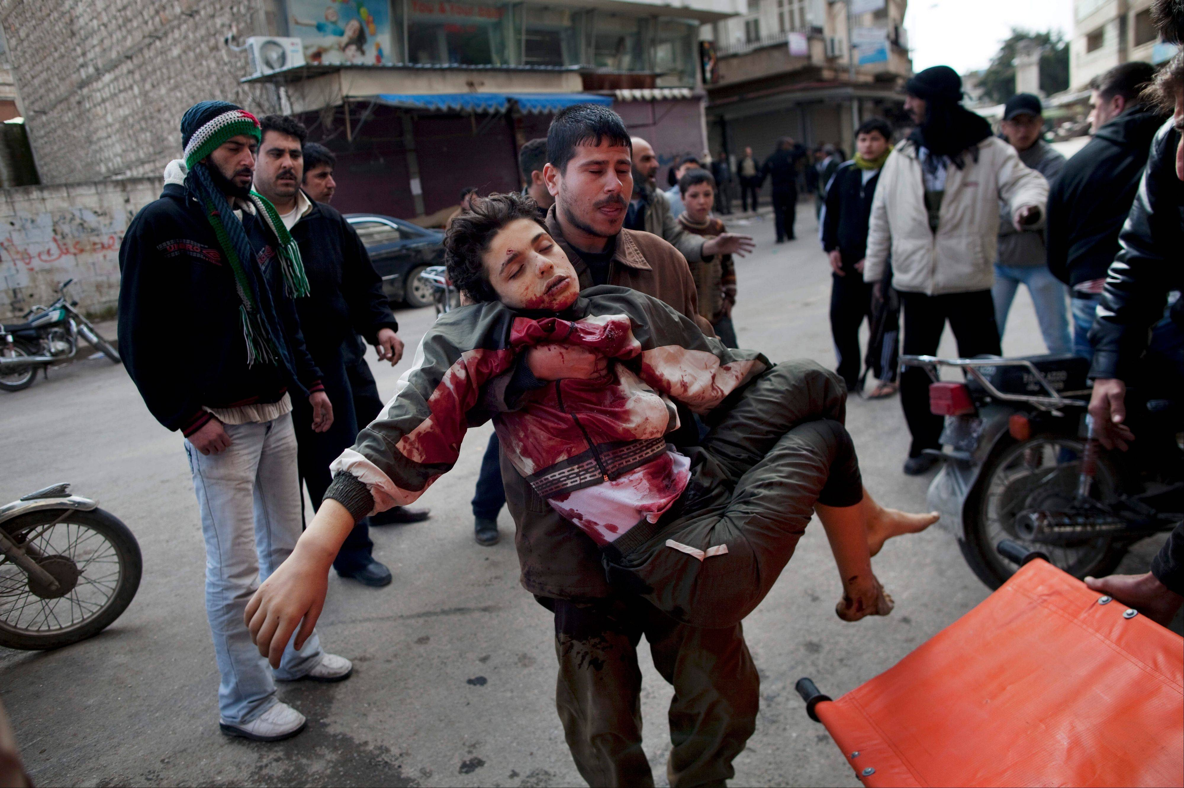 In this Sunday, March 11, 2012 file photo, a man carries a boy who was severely wounded during heavy fighting between Syrian rebels and Syrian Army forces in Idlib, north Syria.