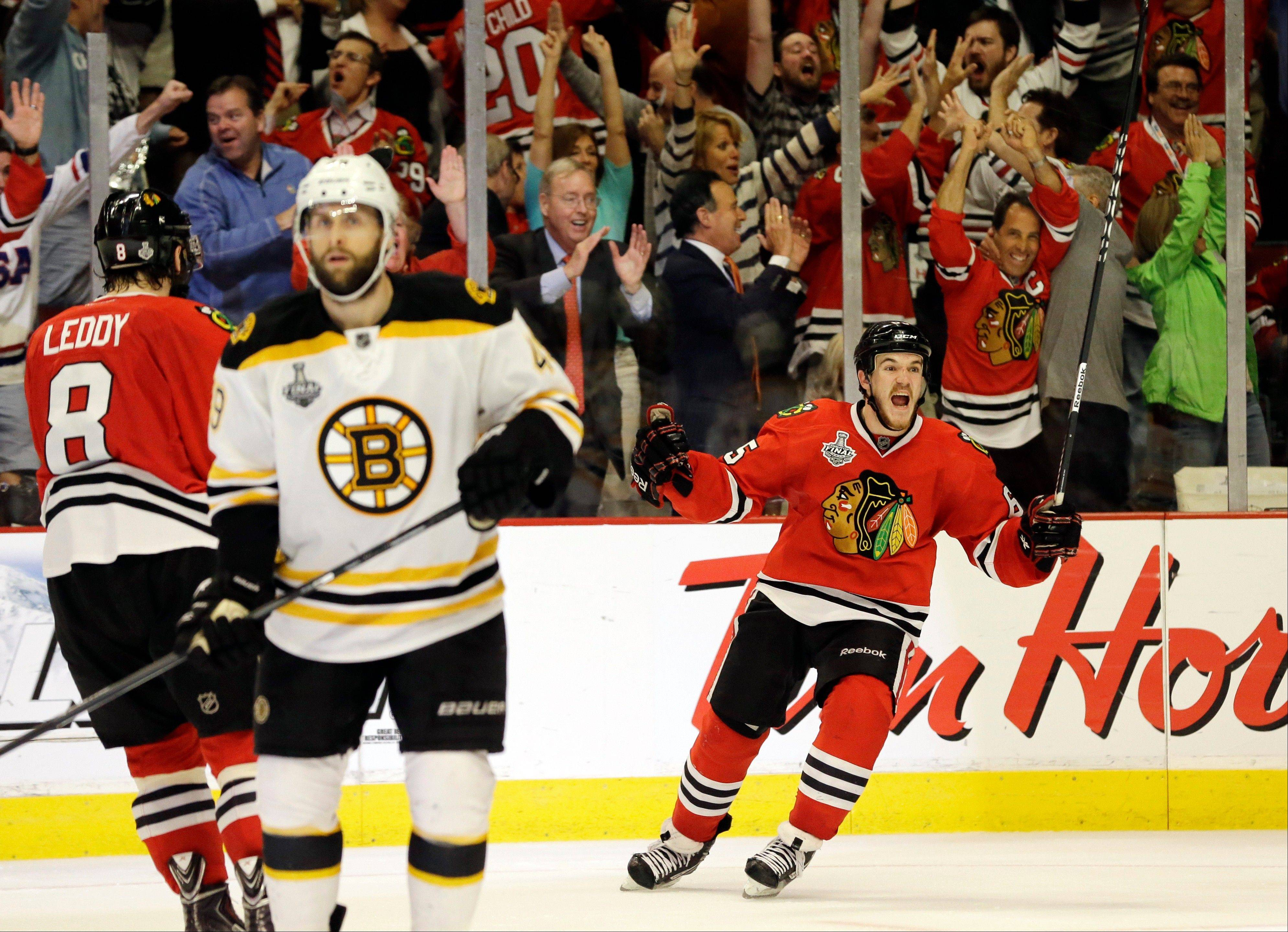 Chicago Blackhawks center Andrew Shaw, right, celebrates after scoring the winning goal during the third overtime period of Game 1 in their NHL Stanley Cup Final hockey series against the Boston Bruins, Thursday, June 13, 2013, in Chicago. (AP Photo/Nam Y. Huh)
