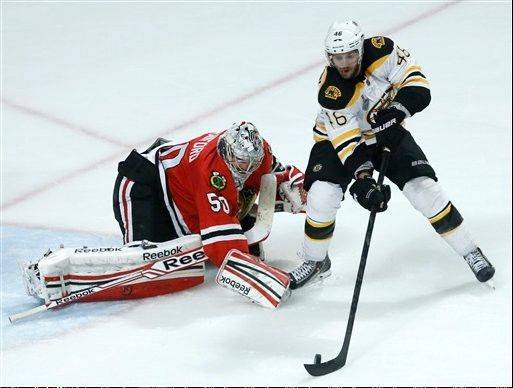 Chicago Blackhawks goalie Corey Crawford (50) keeps Boston Bruins left wing Kaspars Daugavins from getting a shot on goal during the first overtime period of Game 1 in their NHL Stanley Cup Final hockey series,Wednesday, June 12, 2013 in Chicago. (AP Photo/Charles Rex Arbogast)