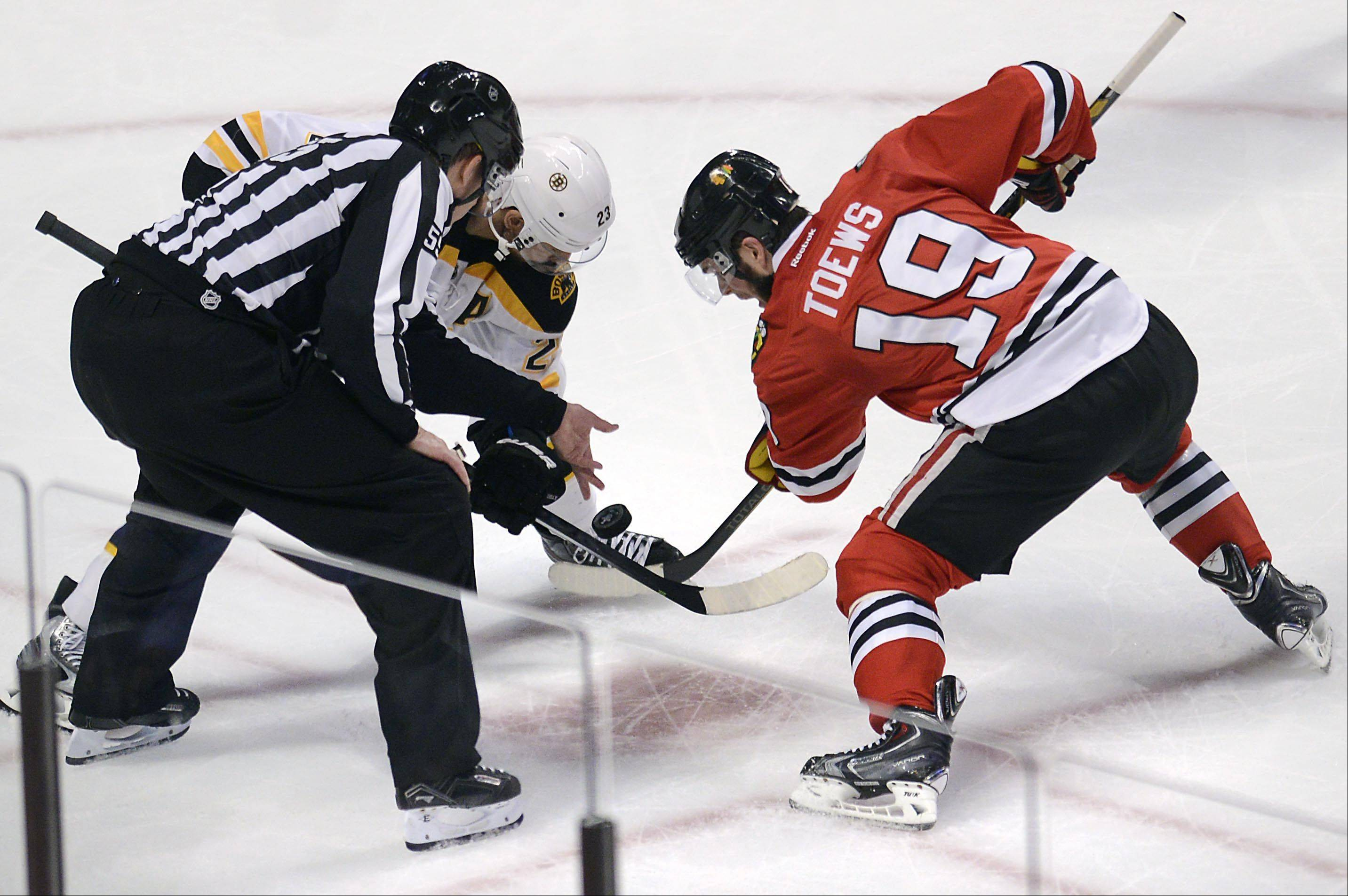 Linesman Shane Heyer drops the puck for a faceoff between Blackhawks center Jonathan Toews and Boston Bruins center Chris Kelly during Game 1 of the Stanley Cup Finals on Wednesday at the United Center in Chicago.