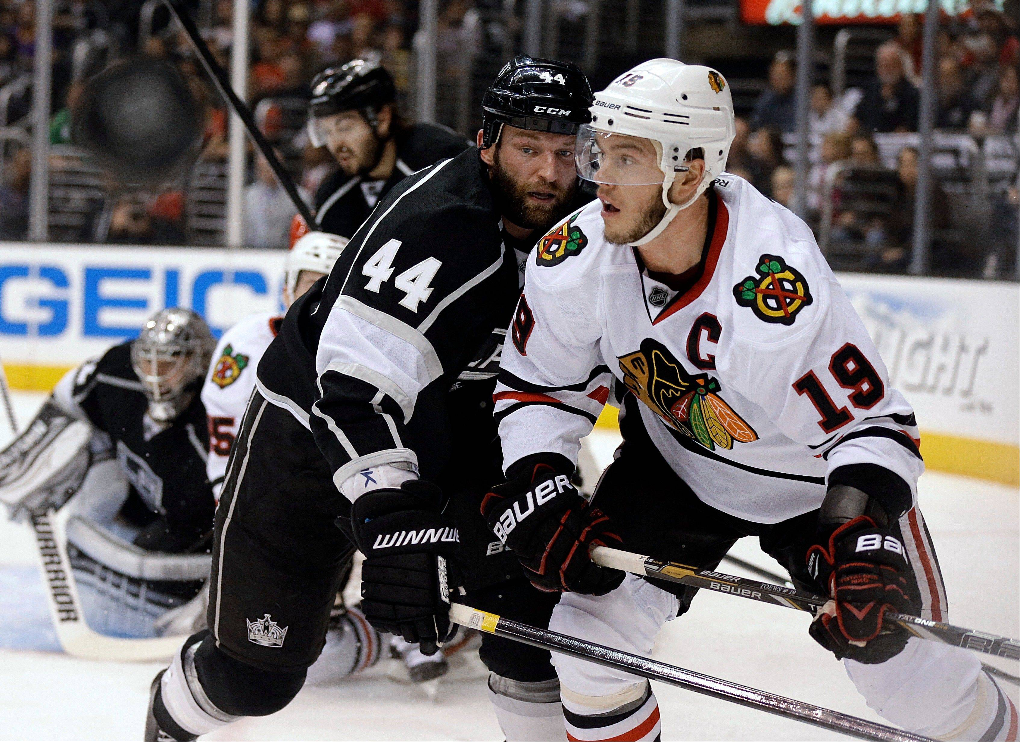 Los Angeles Kings defenseman Robyn Regehr (44) and Chicago Blackhawks center Jonathan Toews (19) work near the Kings goal during the first period of Game 4 of the NHL hockey Stanley Cup playoffs Western Conference finals, in Los Angeles on Thursday, June 6, 2013. (AP Photo/Reed Saxon)