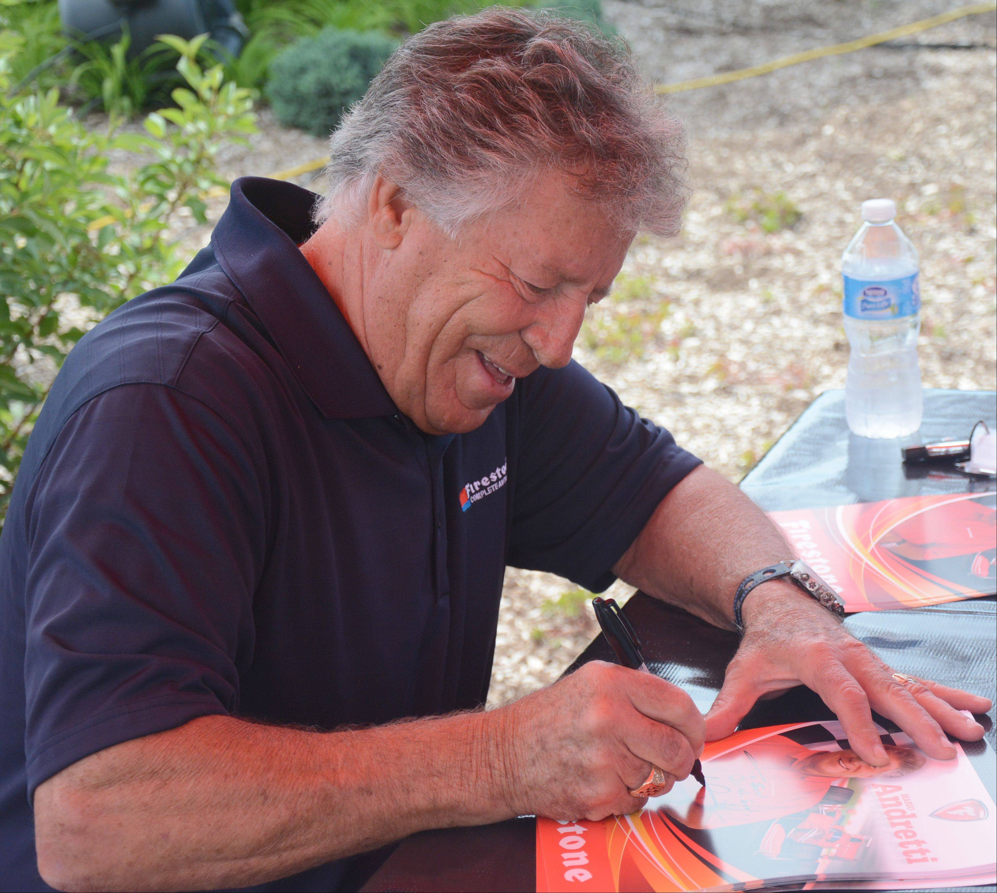 Auto racing legend Mario Andretti signs autographs for fans at the opening of a new Firestone Complete Auto Care store in Palatine Friday.