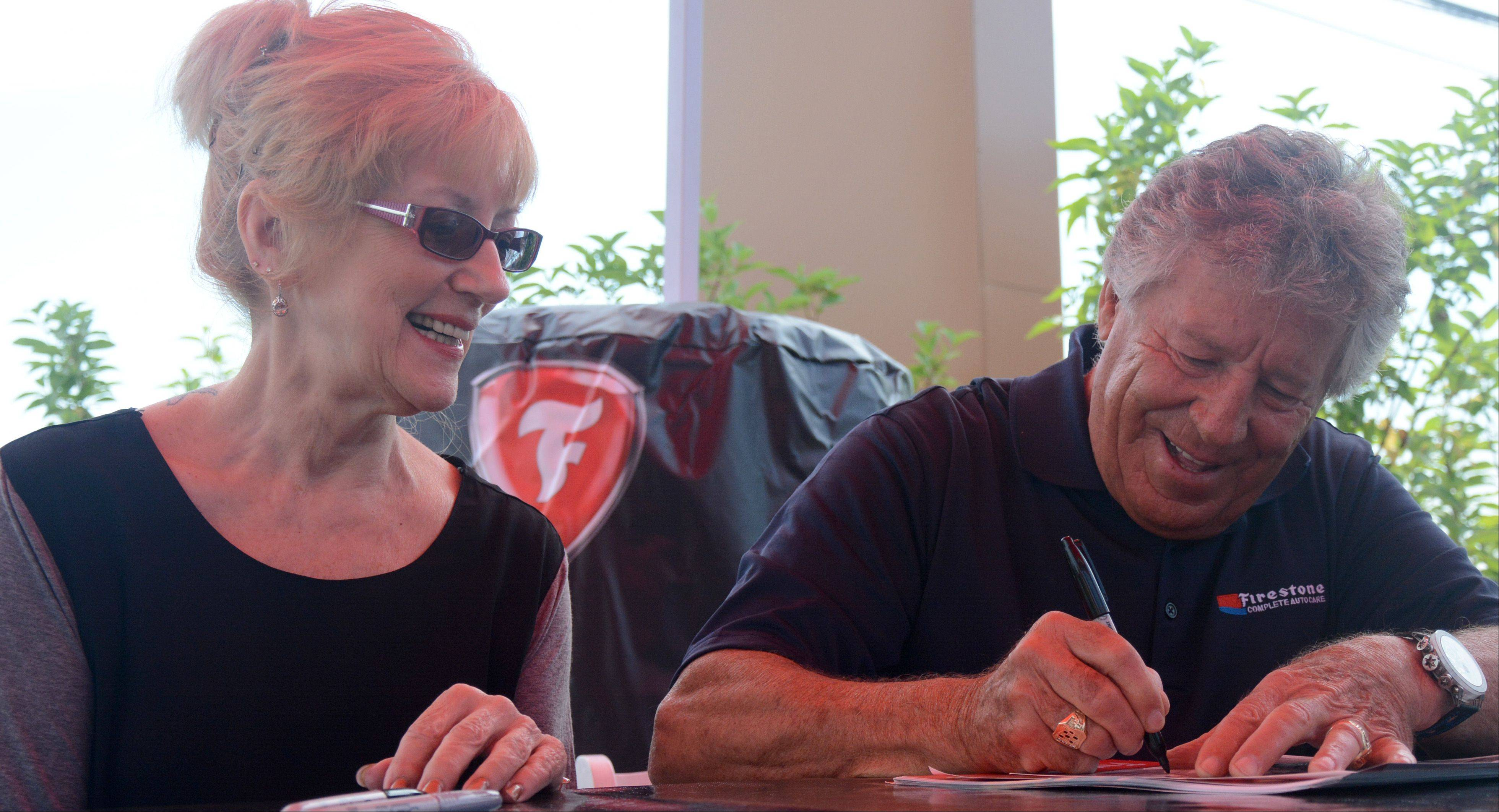 Auto racing legend Mario Andretti signs an autograph for Diane Sipple of Schaumburg on Friday at the opening of a new Firestone Complete Car Care in Palatine. Mann drove in from Wisconsin for the meet-and-greet with Andretti.
