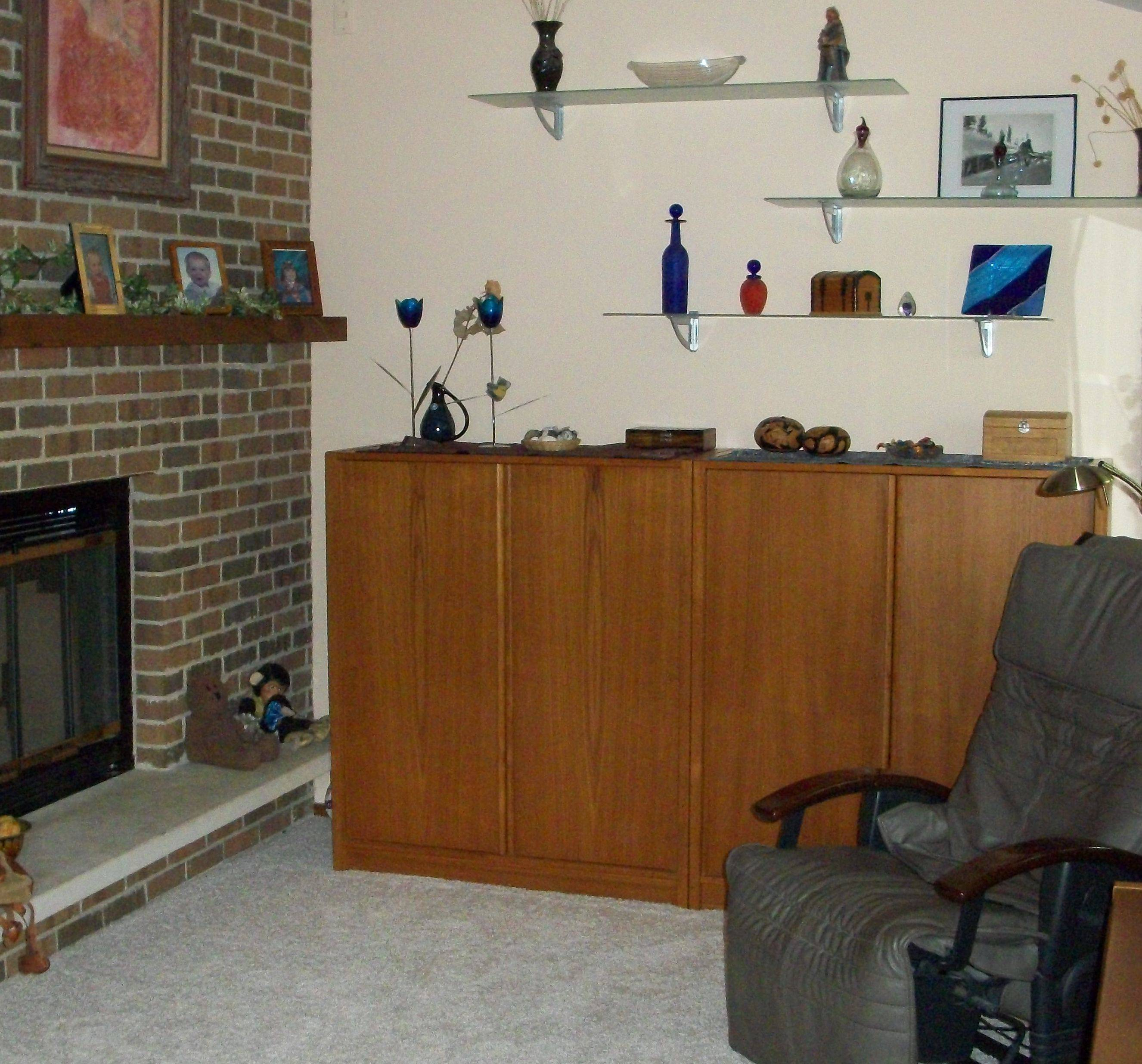 Personal belongings lined the shelves in the master bedroom near the fireplace and on the fireplace mantel prior to when the room was redesigned.