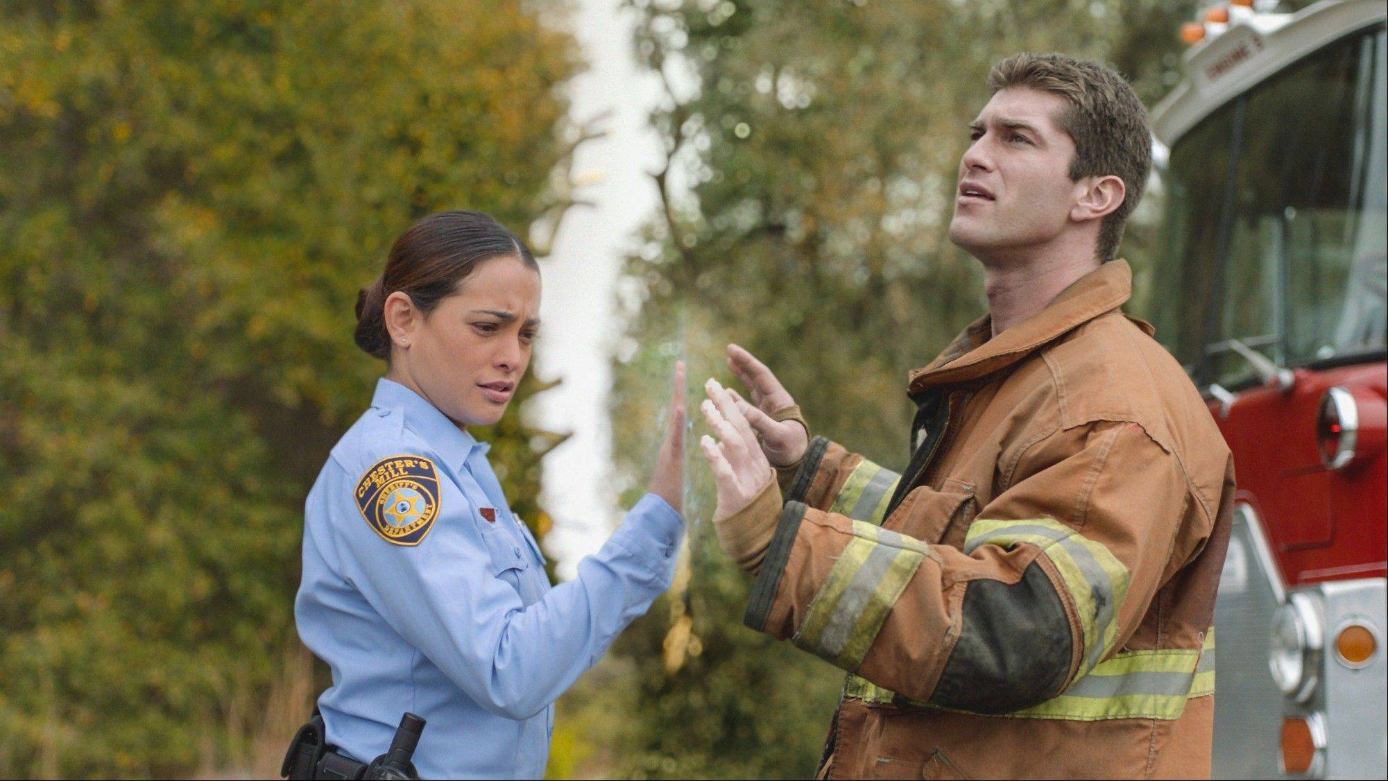 "Deputy Linda (Natalie Martinez), left, and her fianc�, Rusty (Josh Carter), find themselves separated by a massive transparent dome in CBS' ""Under the Dome,"" starting Monday, June 24."