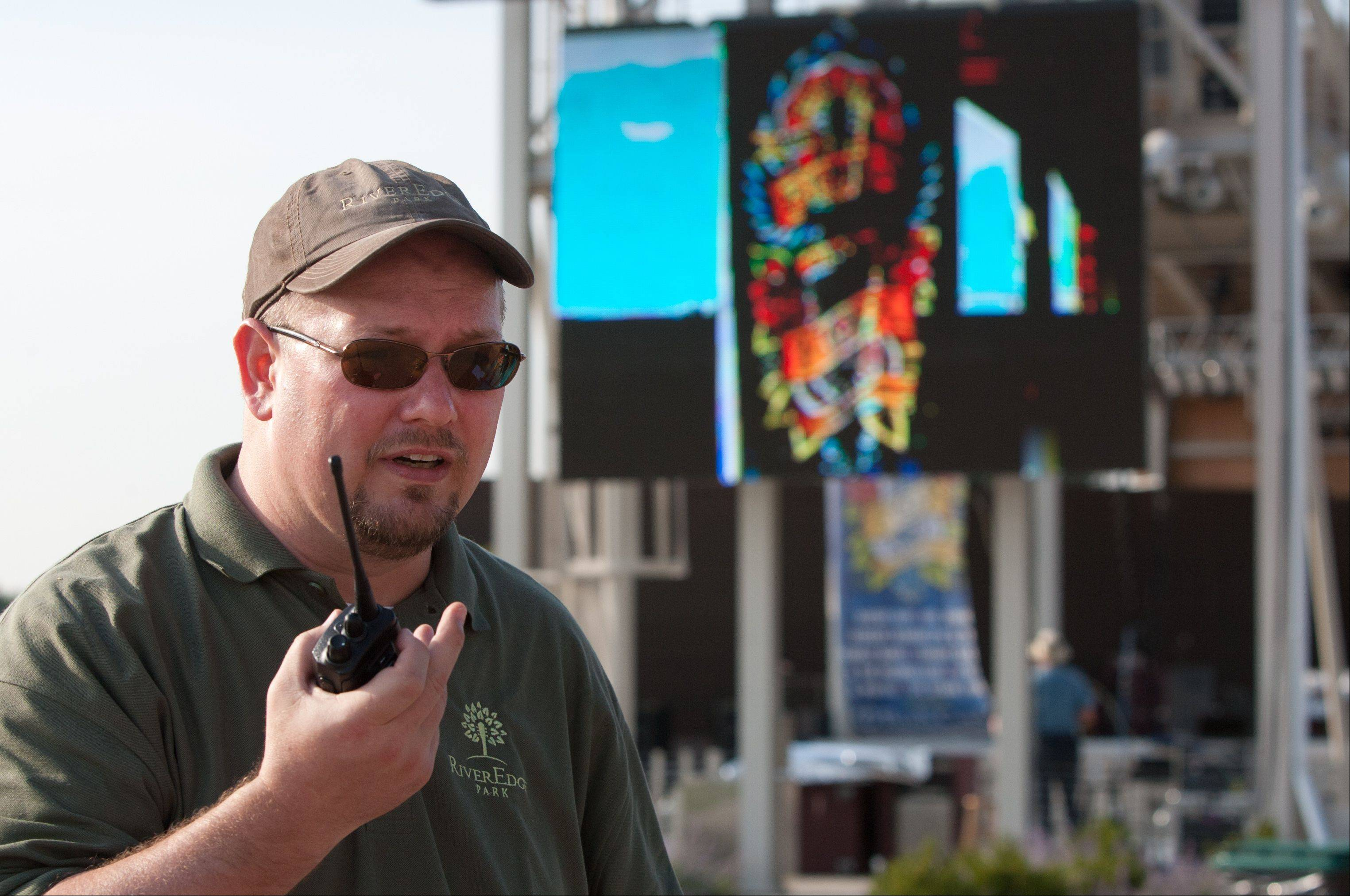 Tim Rater, president and CEO of the Aurora Civic Center Authority, monitors the opening night of RiverEdge Park, coinciding with the 17th annual Blues on the Fox festival.